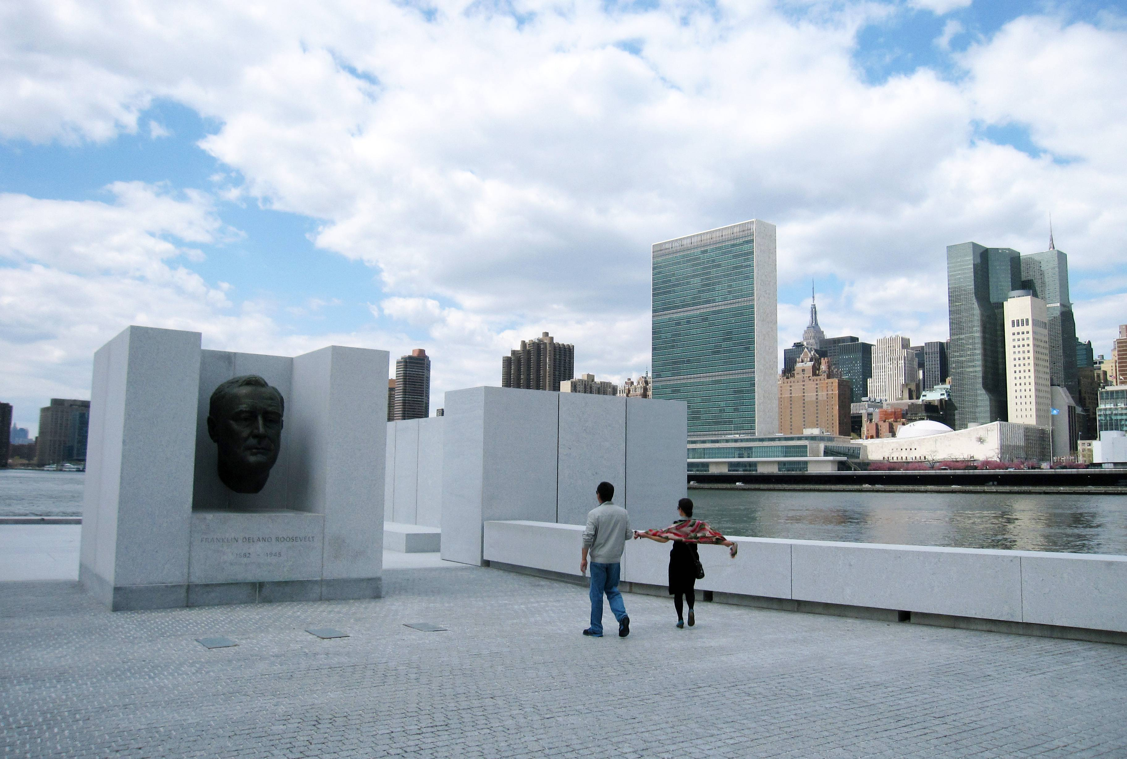 Visitors take pictures in front of a bust of President Franklin D. Roosevelt at Franklin D. Roosevelt Four Freedoms Park, located on Roosevelt Island in New York City. The park, designed by renowned architect Louis I. Kahn, is considered an architectural masterpiece and offers scenic views of the city, including the Manhattan skyline.