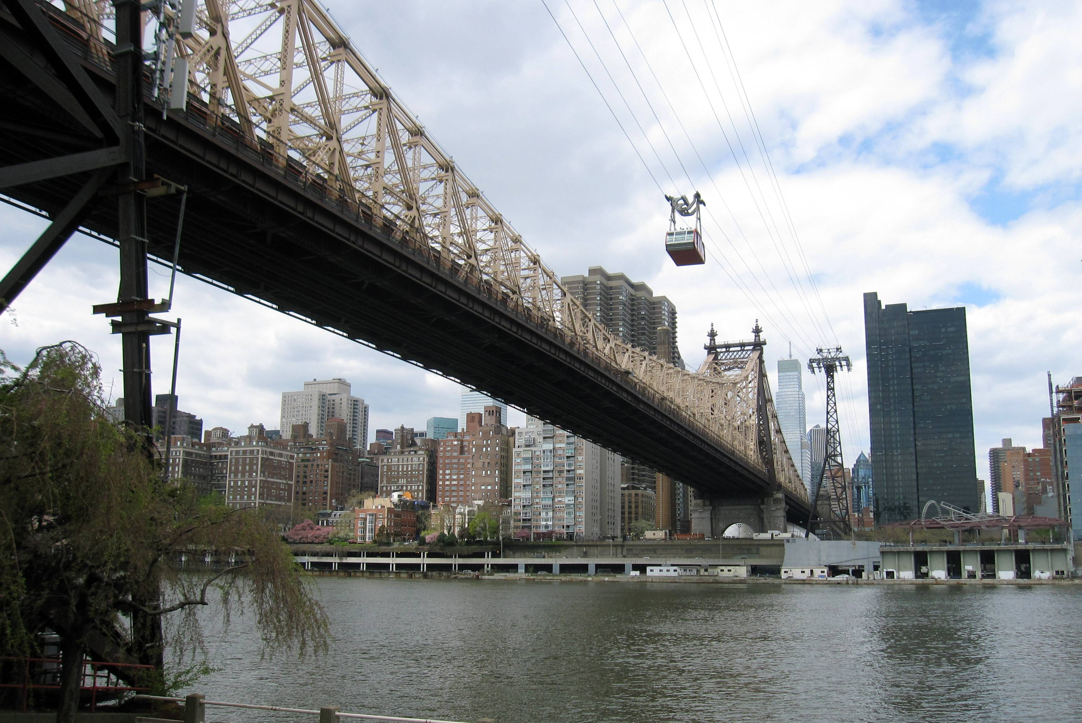 The Roosevelt Island Tram above the Ed Koch Queensborough Bridge, crosses the East River to Roosevelt Island in New York City.