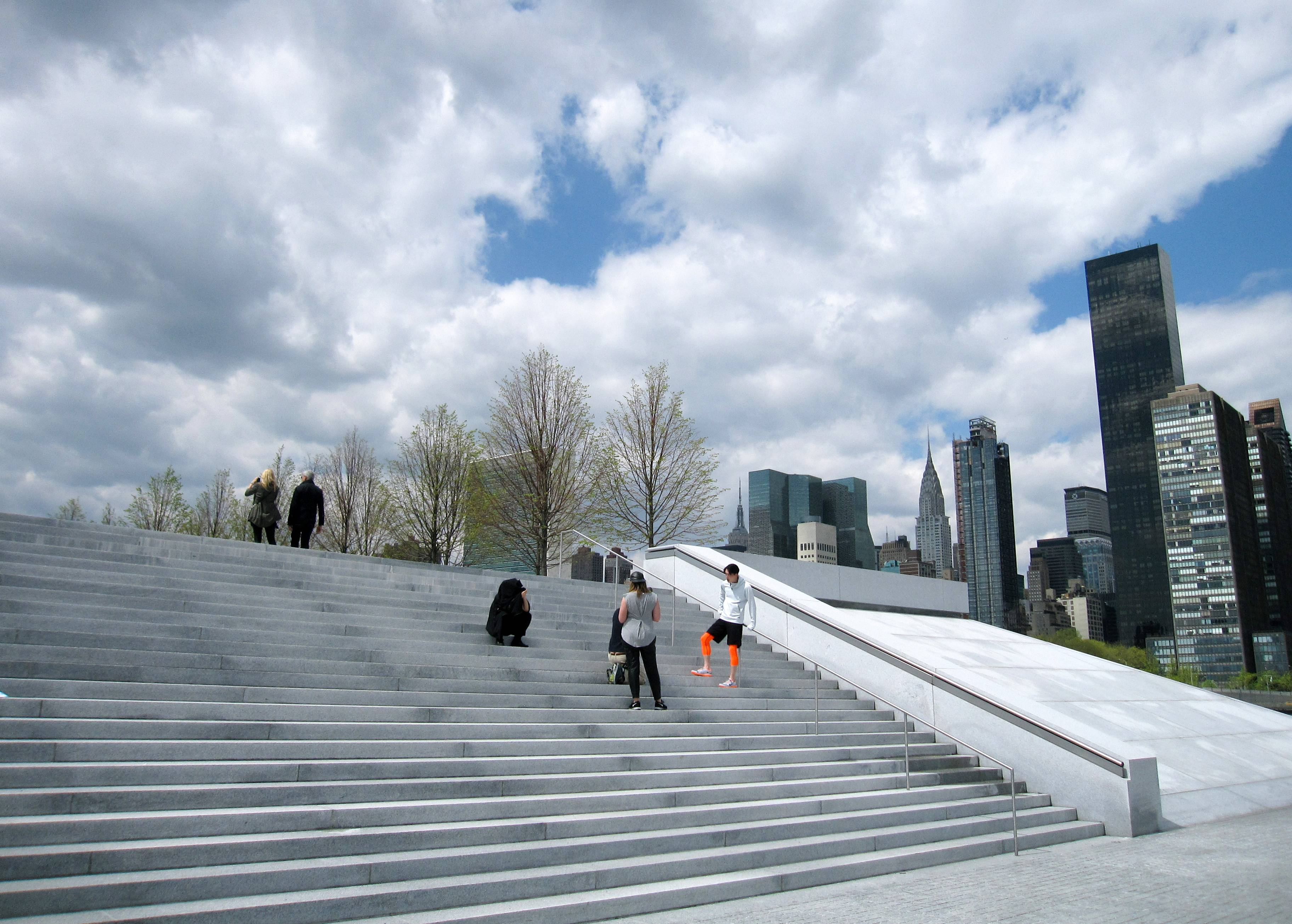 Visitors stand on the steps at Franklin D. Roosevelt Four Freedoms Park, located on Roosevelt Island in New York City. The park, designed by renowned architect Louis I. Kahn, is considered an architectural masterpiece and offers scenic views of the city.