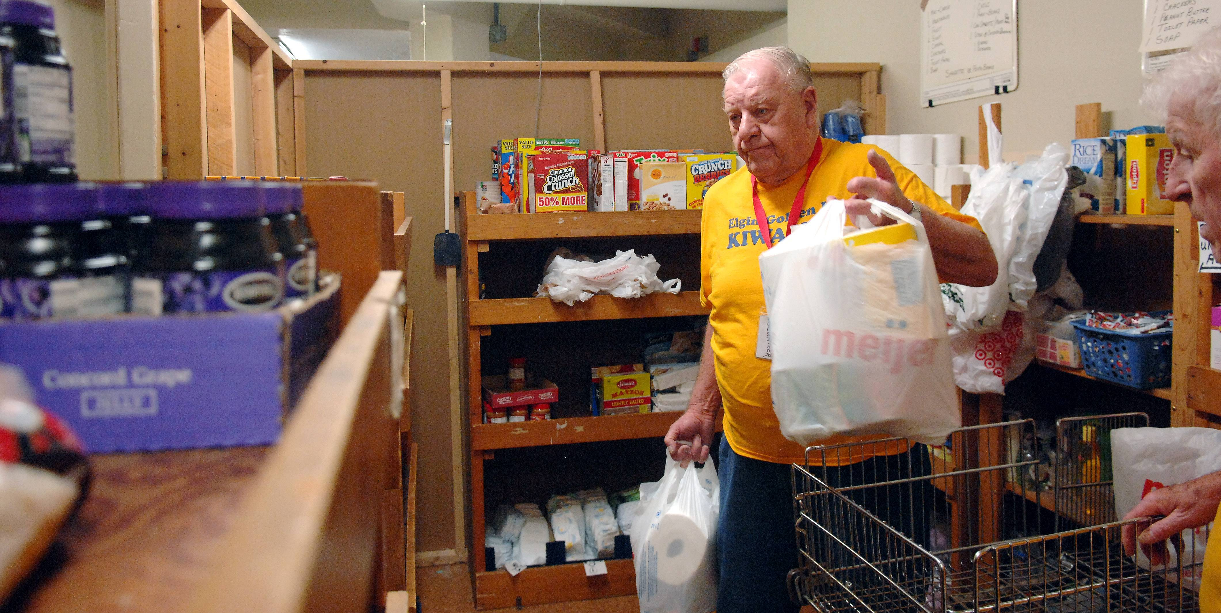 Volunteer Charles Awe of Elgin brings out bags of groceries he and fellow Golden K Kiwanis member Al Mink packed up Monday for a family at All People's Interfaith Food Pantry in Elgin.