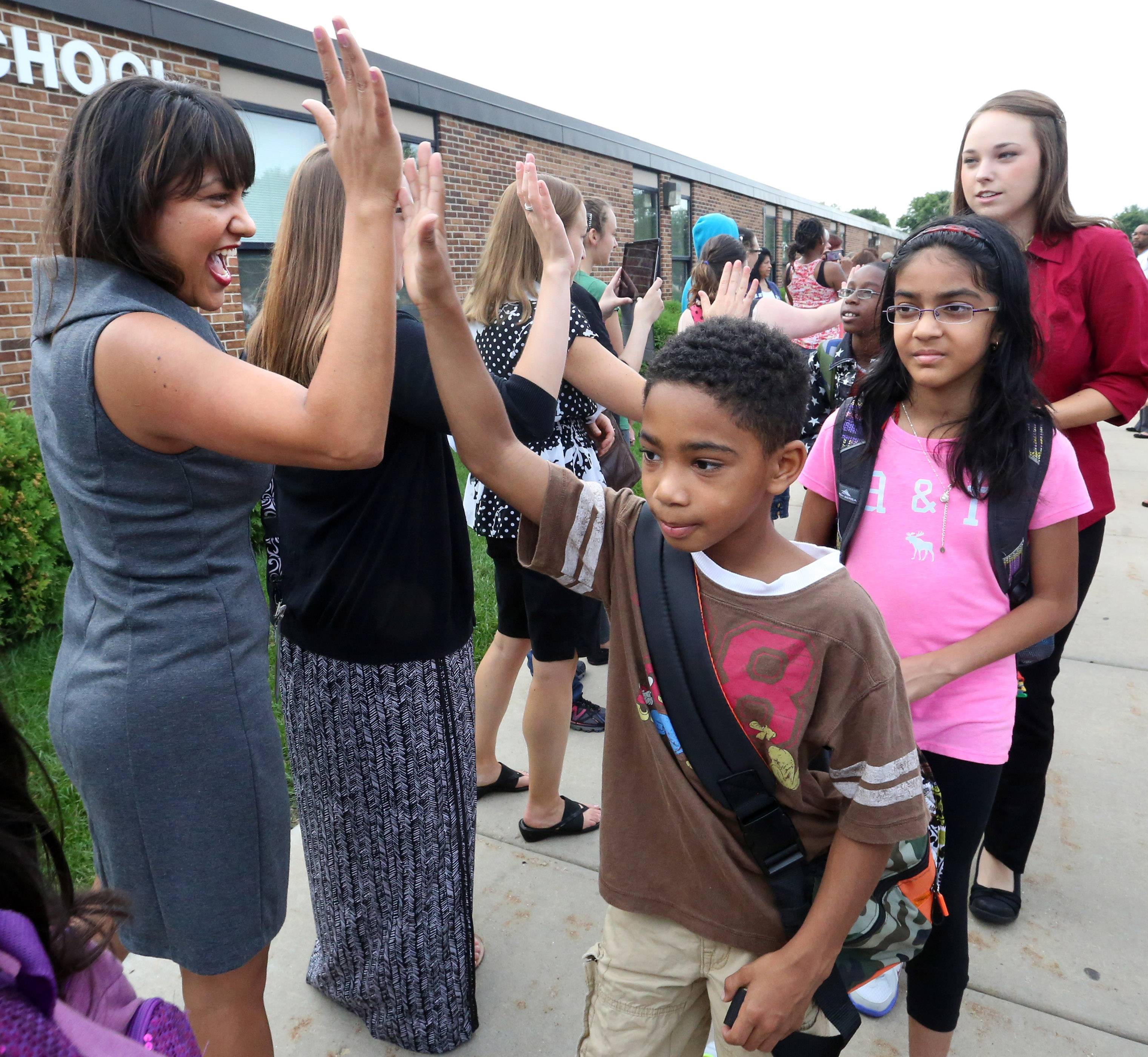 Fourth-grader Chase Hampton gets a high-five from English teacher Carmen Bustamante as he walks through a welcome tunnel of parents and teachers on the first day of school Tuesday at Anne Fox Elementary in Hanover Park.