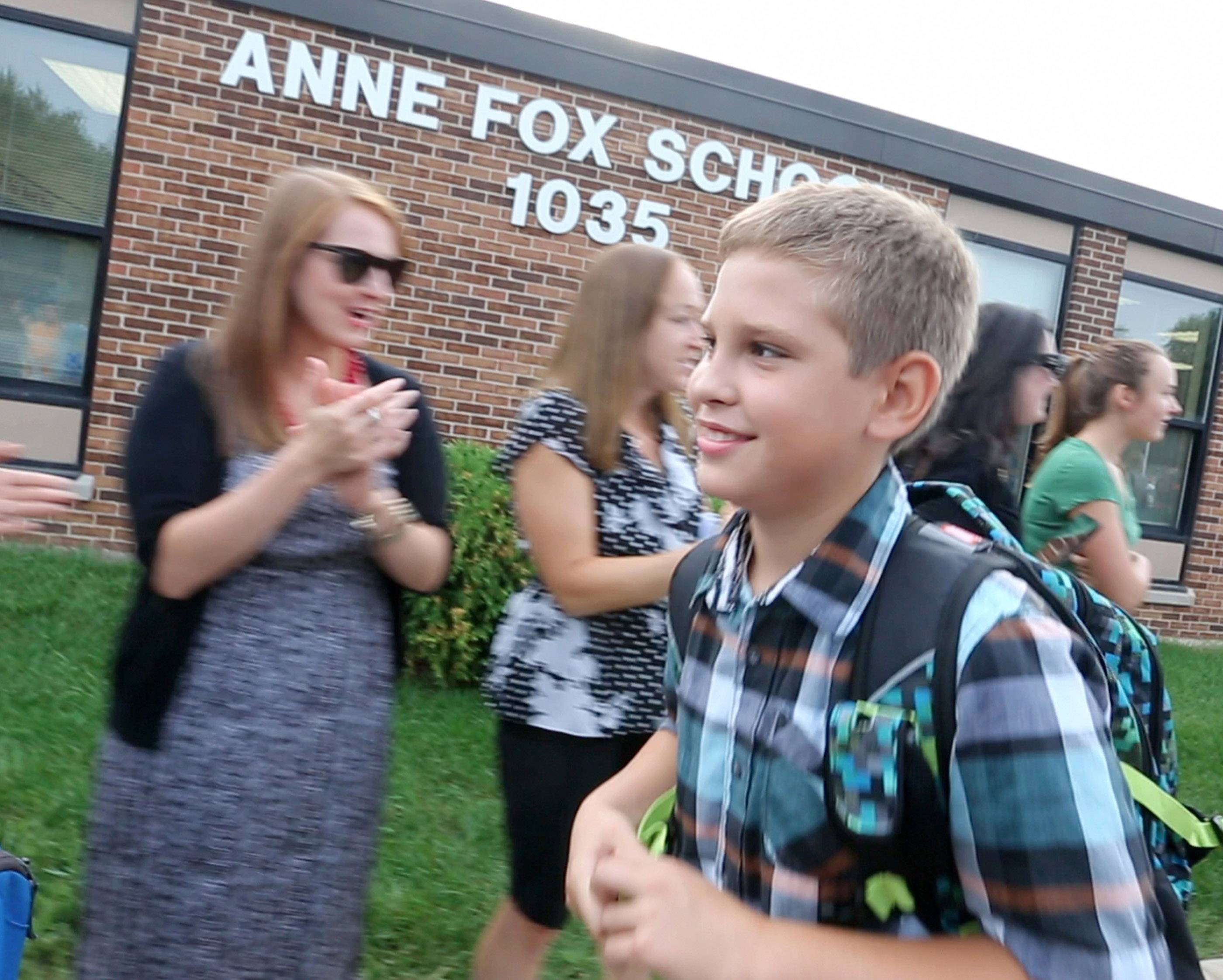 Aiden Dobrzynski walks through a welcome tunnel of parents and teachers on the first day of school Tuesday at Anne Fox Elementary in Hanover Park.