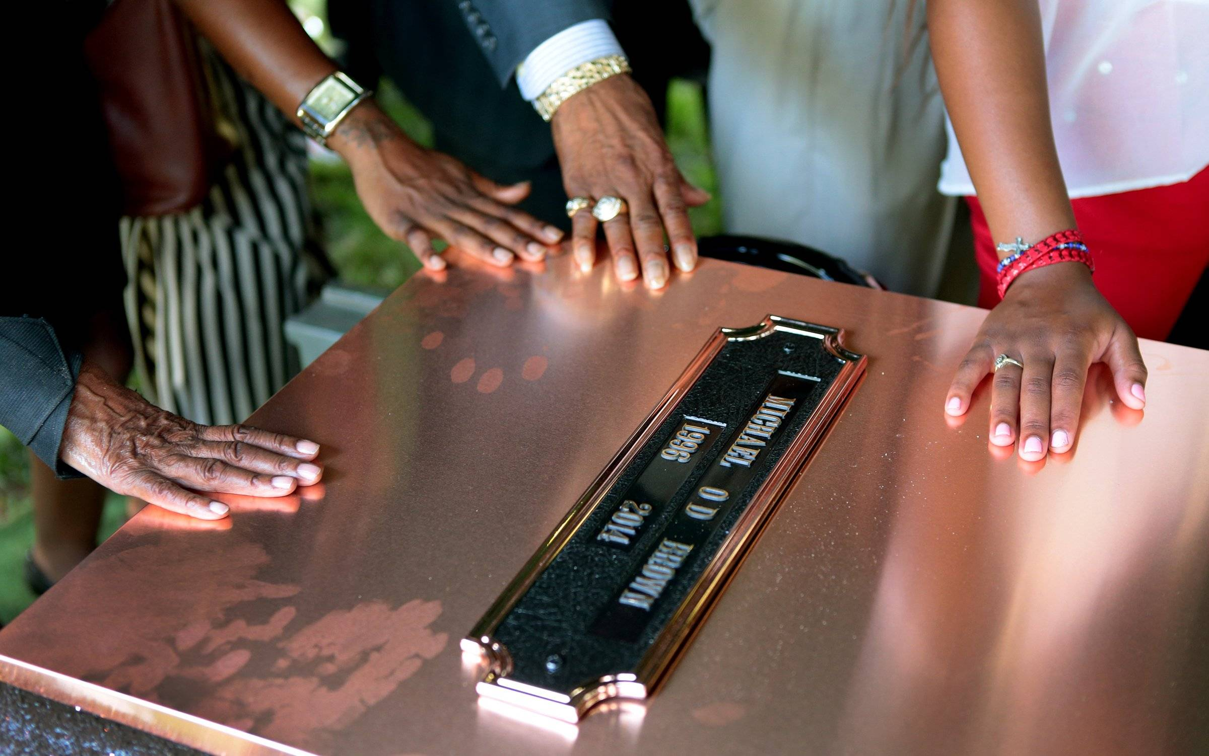 Family members touch the copper top of the vault containing the casket of Michael Brown during his funeral on Monday, Aug. 25, 2014, in Normandy, Mo. Hundreds of people gathered to say goodbye to Brown, who was shot and killed by a Ferguson, Mo., police officer on Aug. 9.