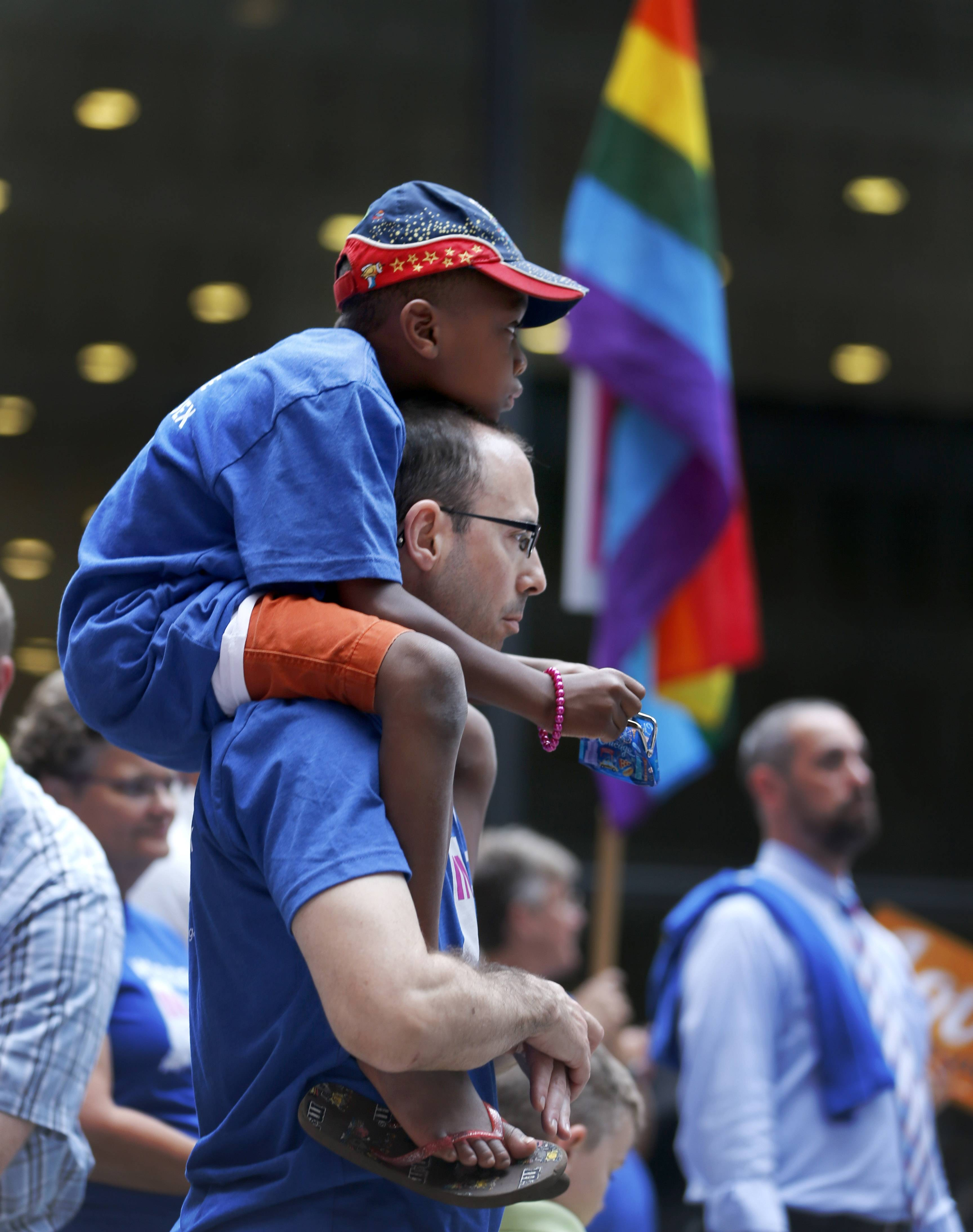 George Sloan, from Chicago, holds his son Sloan D'Souza on his shoulders as they attend a rally in support of gay marriage in Wisconsin and Indiana, at the federal plaza Monday, Aug. 25, 2014, in Chicago. The Chicago-based 7th U.S. Circuit Court of Appeals will hear arguments Tuesday on gay marriage fights from Indiana and Wisconsin, setting the stage for one ruling. Each case deals with whether statewide gay marriage bans violate the Constitution.