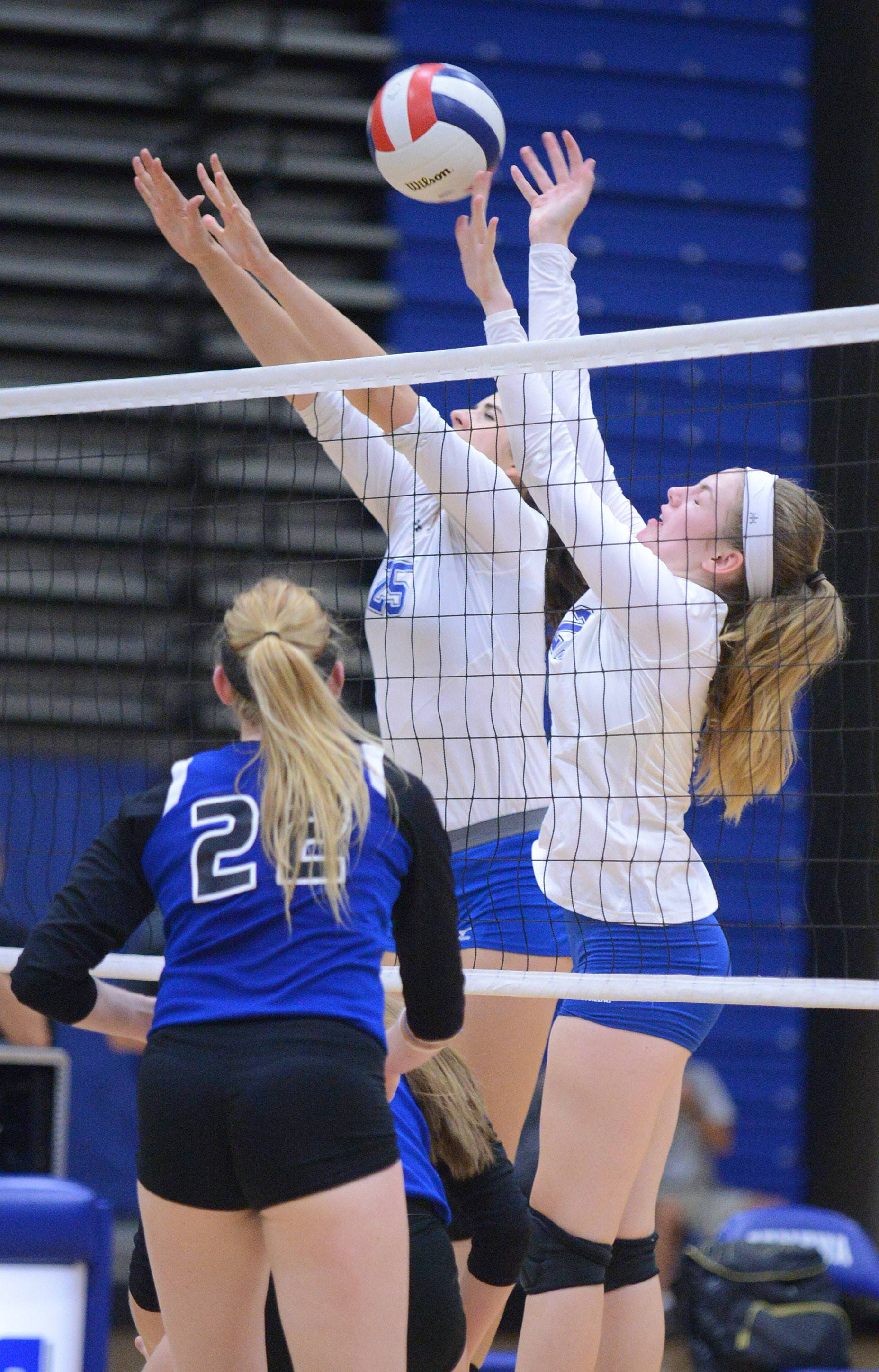 Rosary's Joanna Wedge, left, stands by as Geneva's Ally Barrett, center, and Megan Schmidt, right, block a spike by the Royals in the second match on Tuesday.