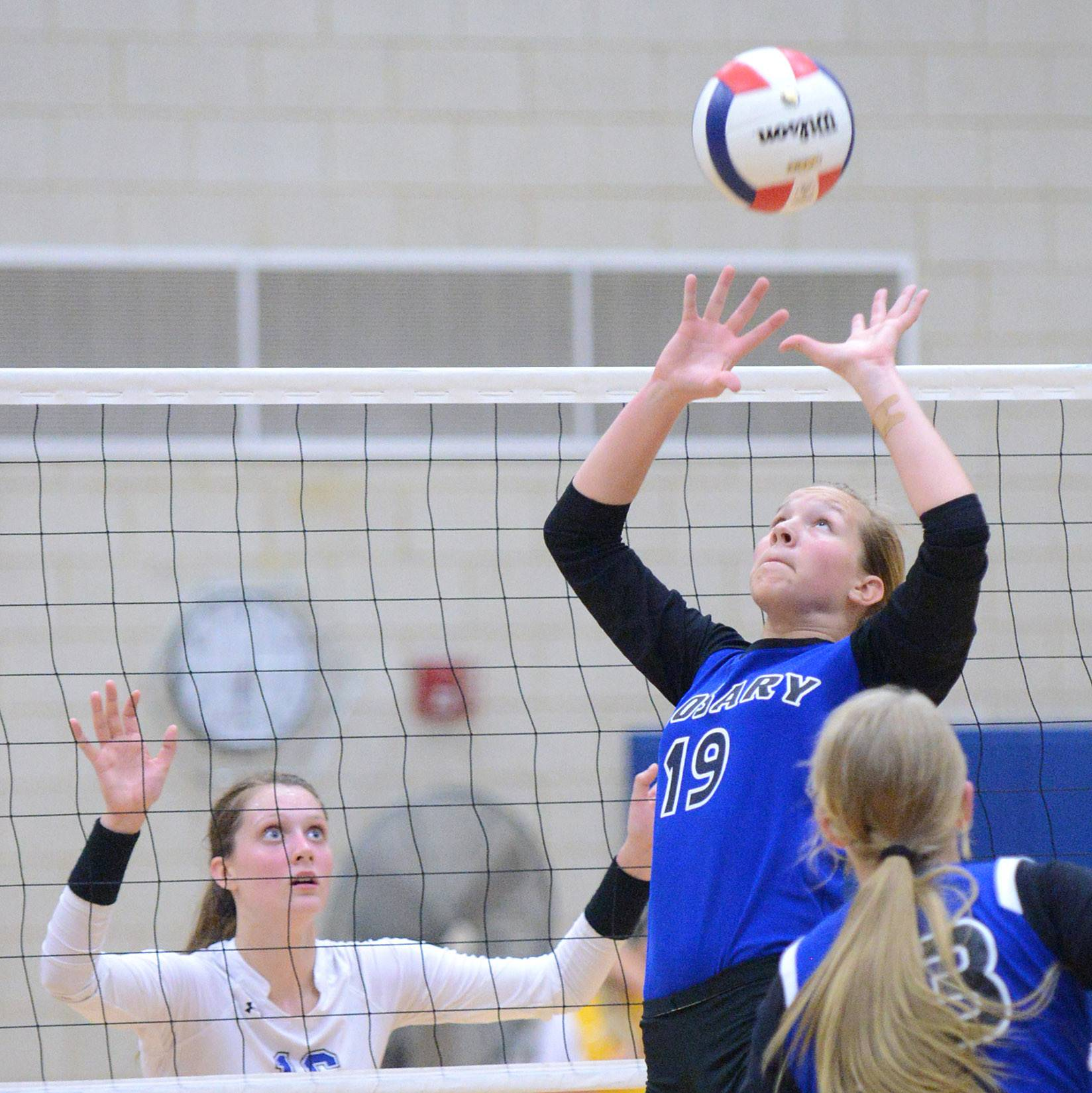 Geneva's Hannah Lanasa, left, readies for the ball as Rosary's Julia Gauthier sets up a teammate Tuesday in Geneva.