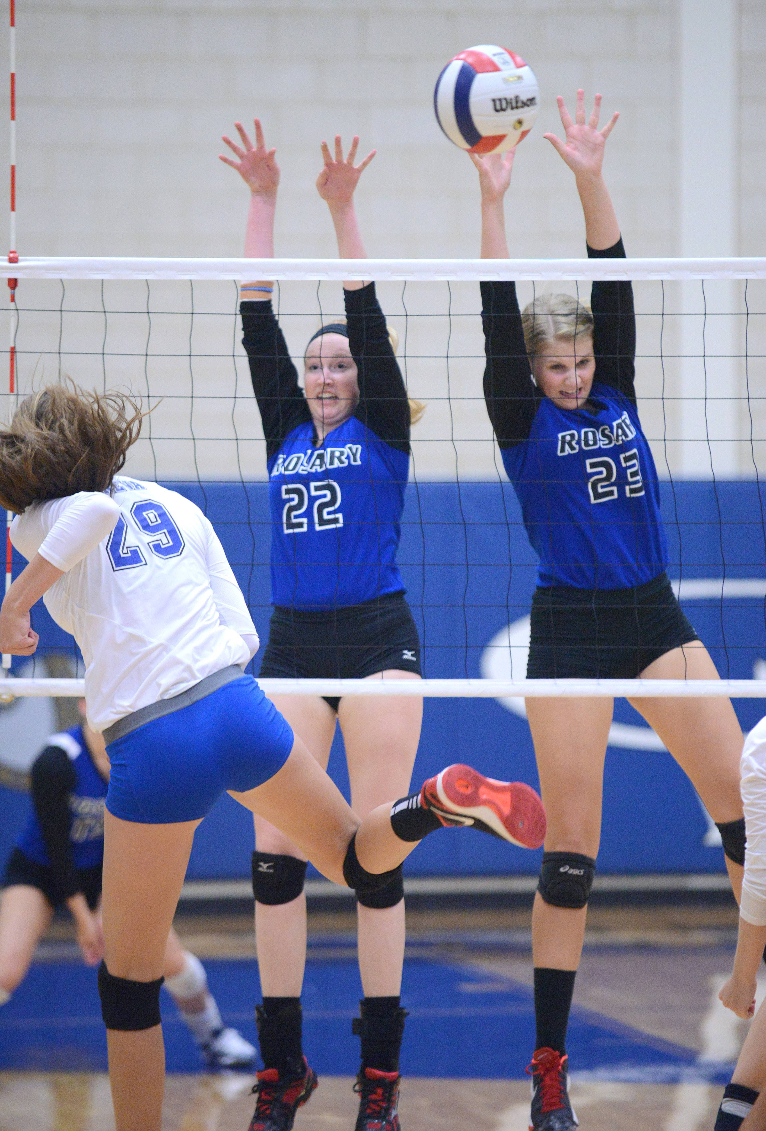Geneva's Grace Loberg spikes over the net to Rosary's Joanna Wedge (22) and Michaela Ping (23) in the first match on Tuesday.