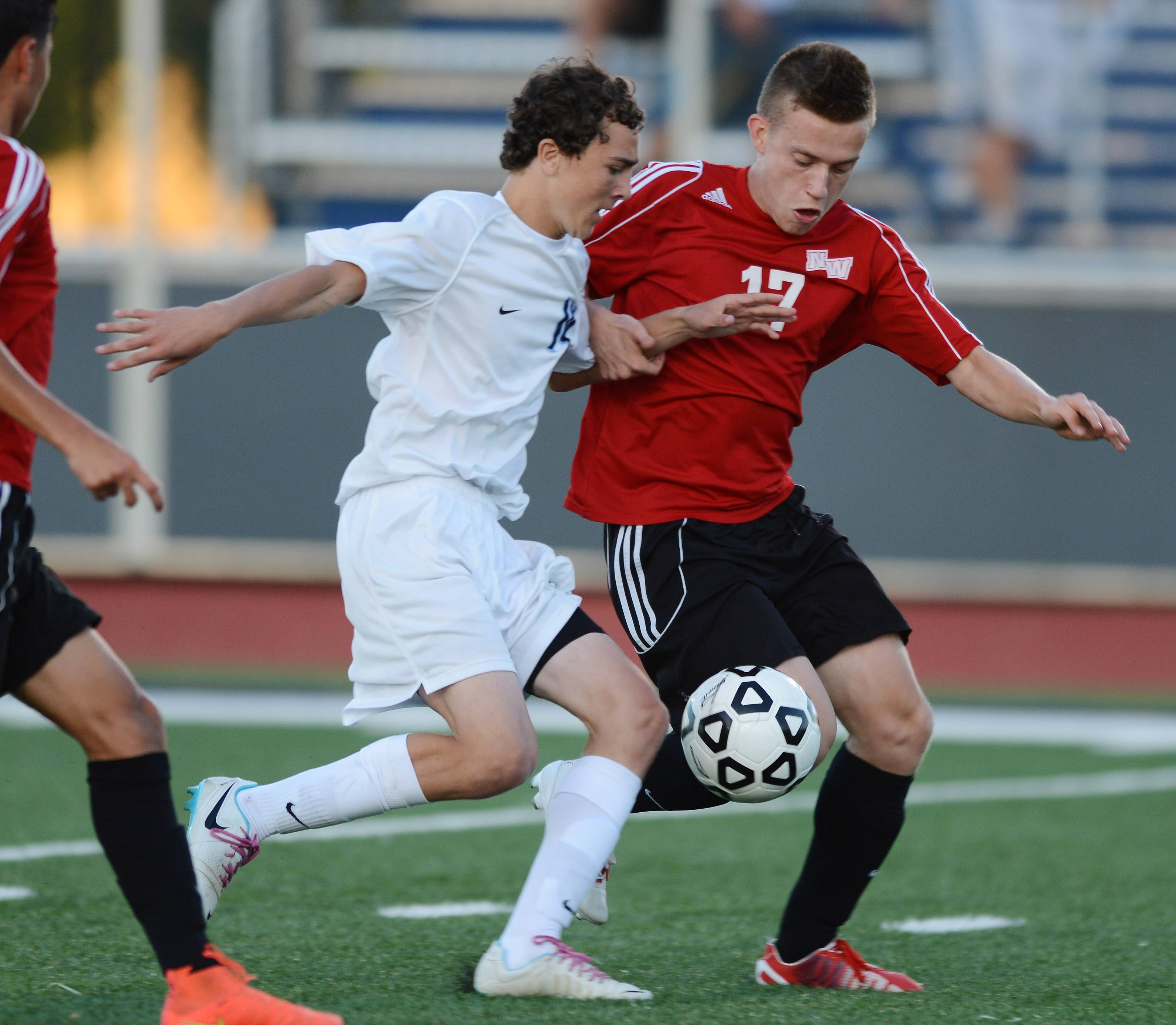 Chris Cooney, left, of Prospect and Emin Ademi of Niles West make contact as they pursue the ball during Tuesday's game in Mount Prospect.