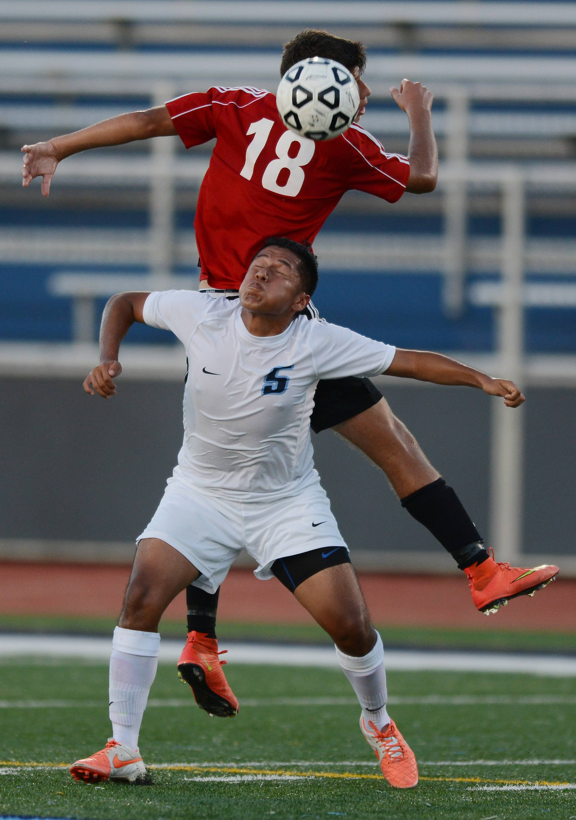 Prospect's Miguel Cruz, front, positions himself behind Niles West's Denis Soldo for a header during Tuesday's game in Mount Prospect.