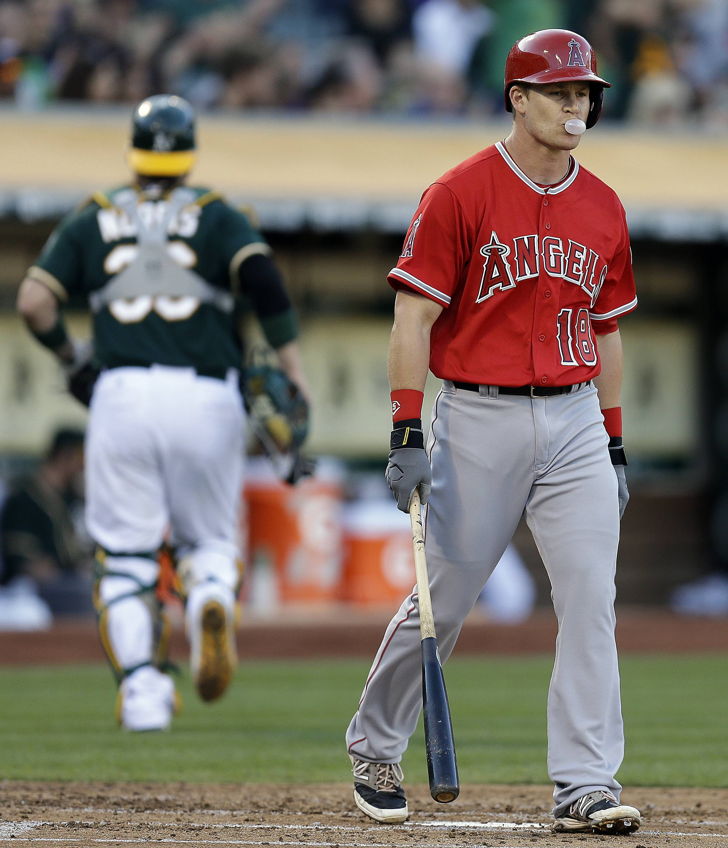 Los Angeles Angels' Gordon Beckham, right, blows a bubble after being called out on strikes from Oakland Athletics' Jon Lester in the second inning of a baseball game Saturday, Aug. 23, 2014, in Oakland, Calif.