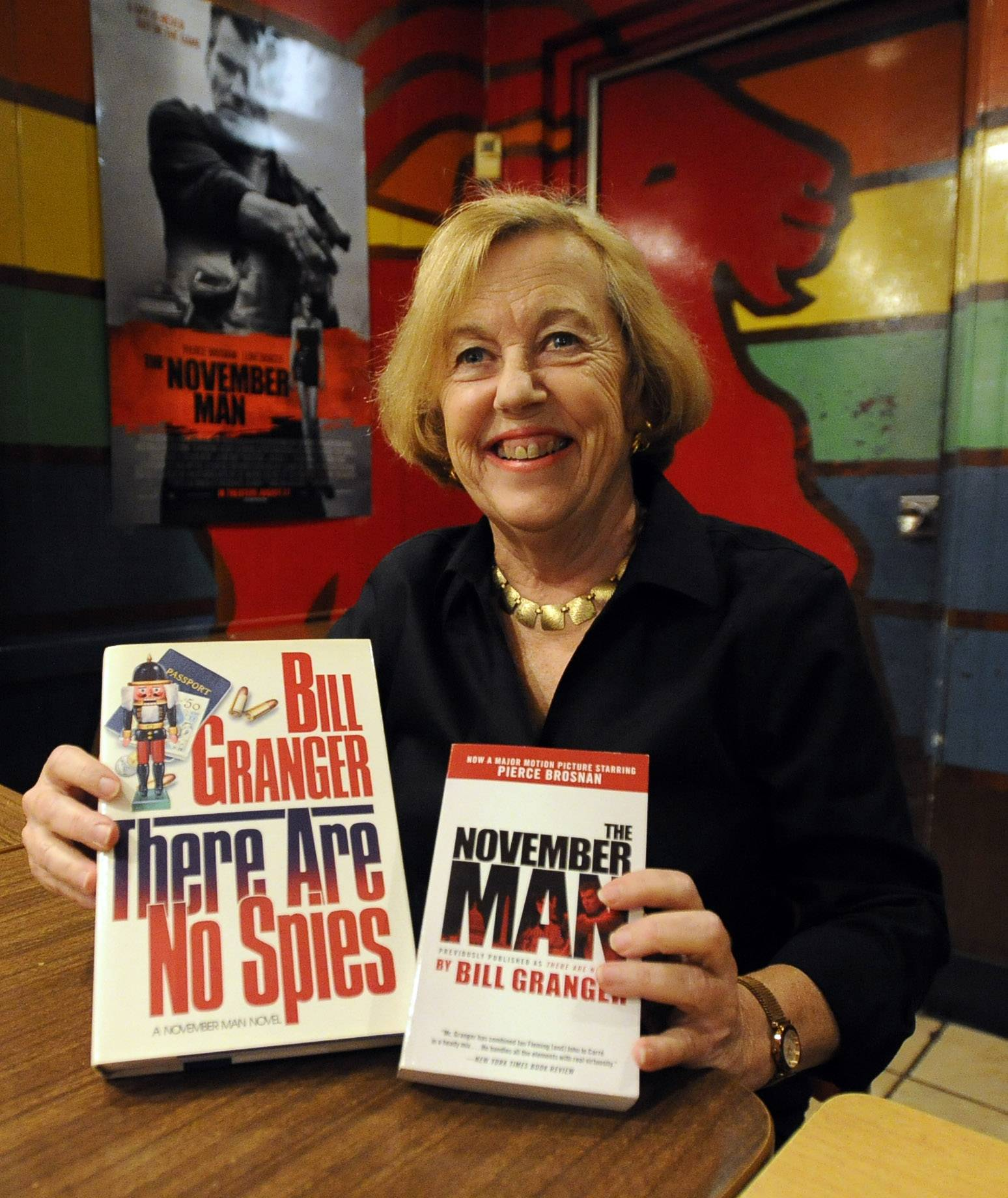 "Lori Granger, widow of newspaperman and novelist Bill Granger, shows off his books Wednesday in Chicago. The seventh in his ""November Man"" series was adapted for the silver screen."