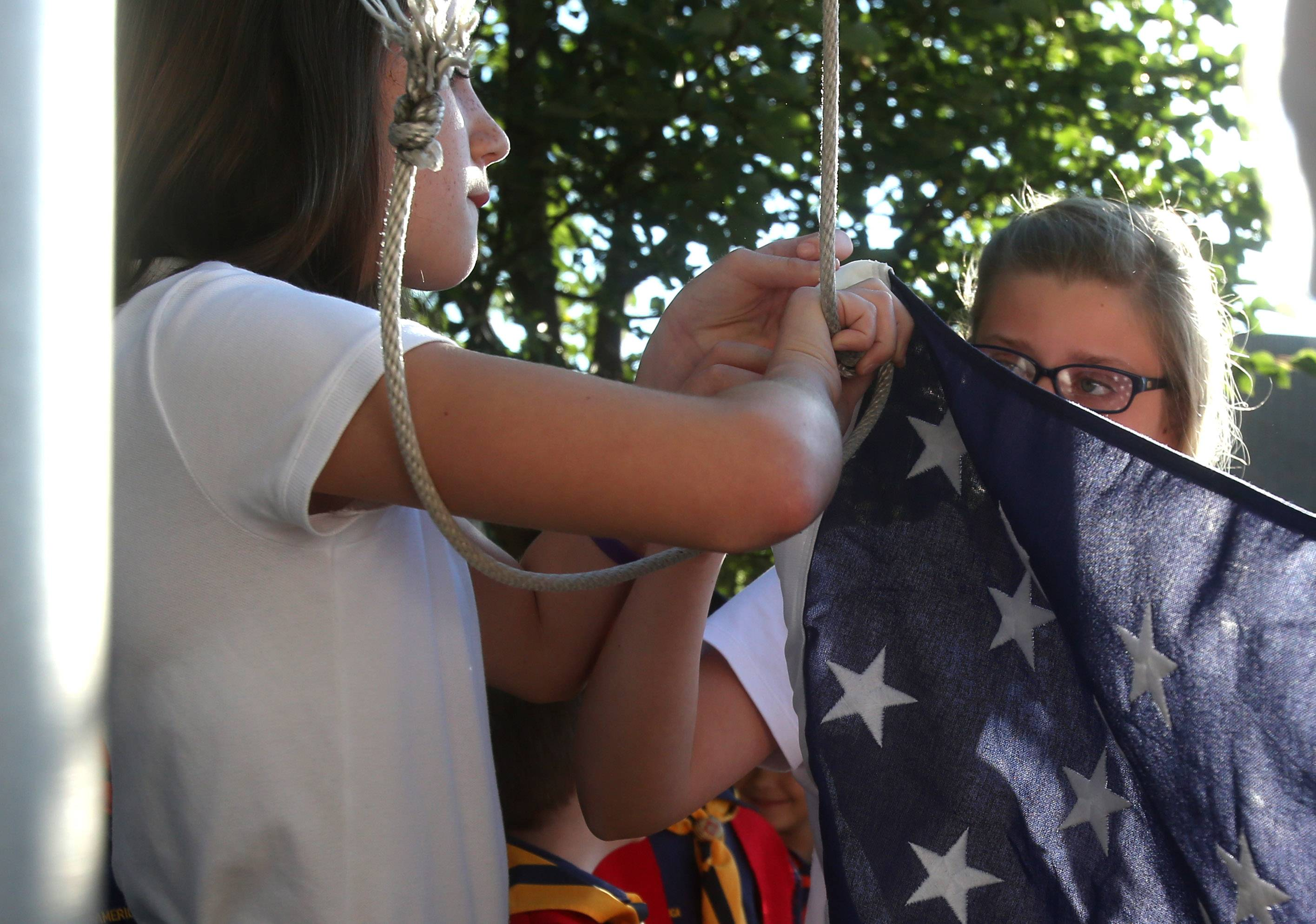 Ani Boghossian, left, and Elizabeth Wessel prepare to raise a new U.S. flag Wednesday during a short ceremony before classes at St. James the Apostle School in Glen Ellyn.