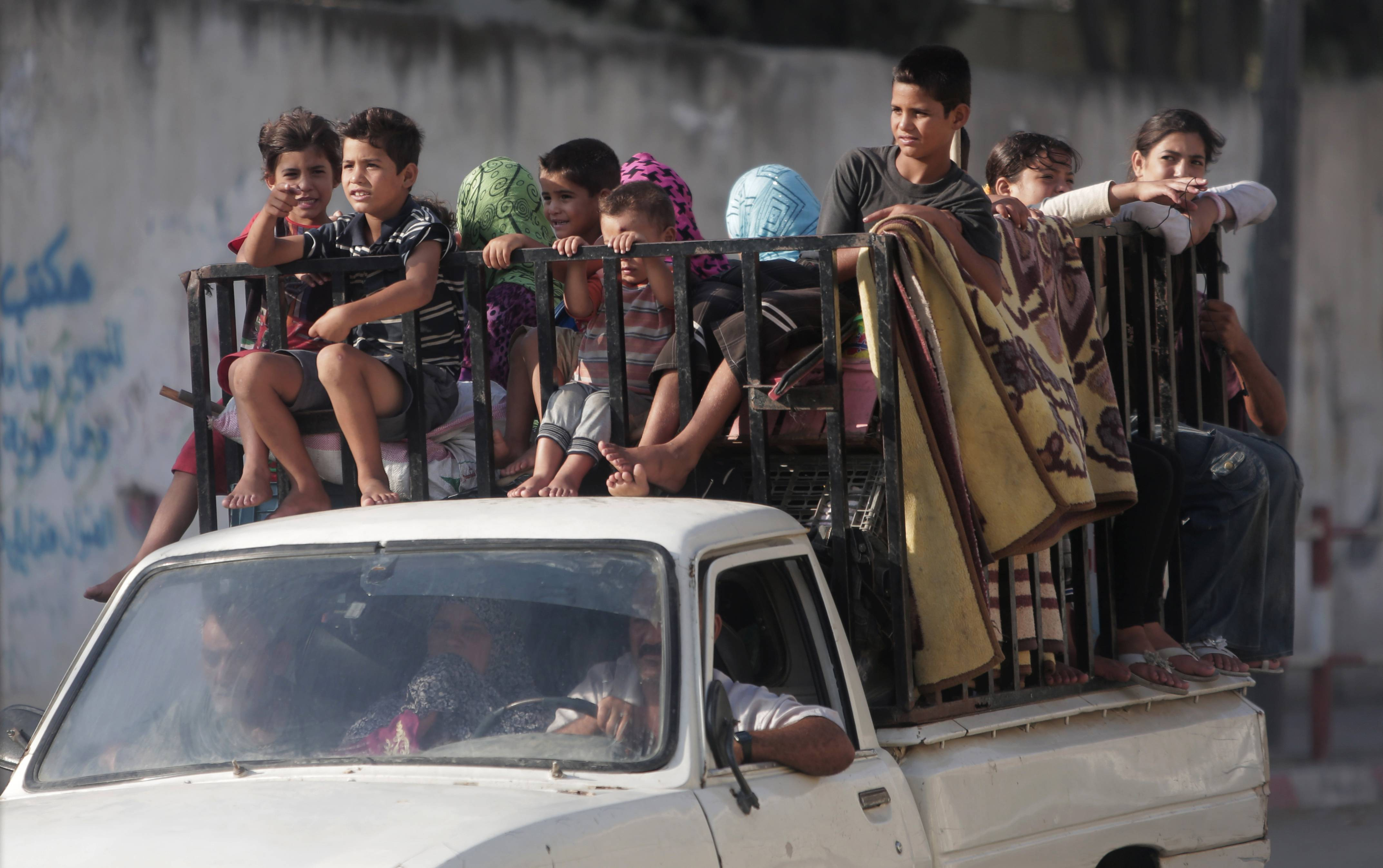 Palestinians with their belongings drive back to their homes in Gaza City's Shijaiyah neighborhood, Wednesday, Aug. 27, 2014.