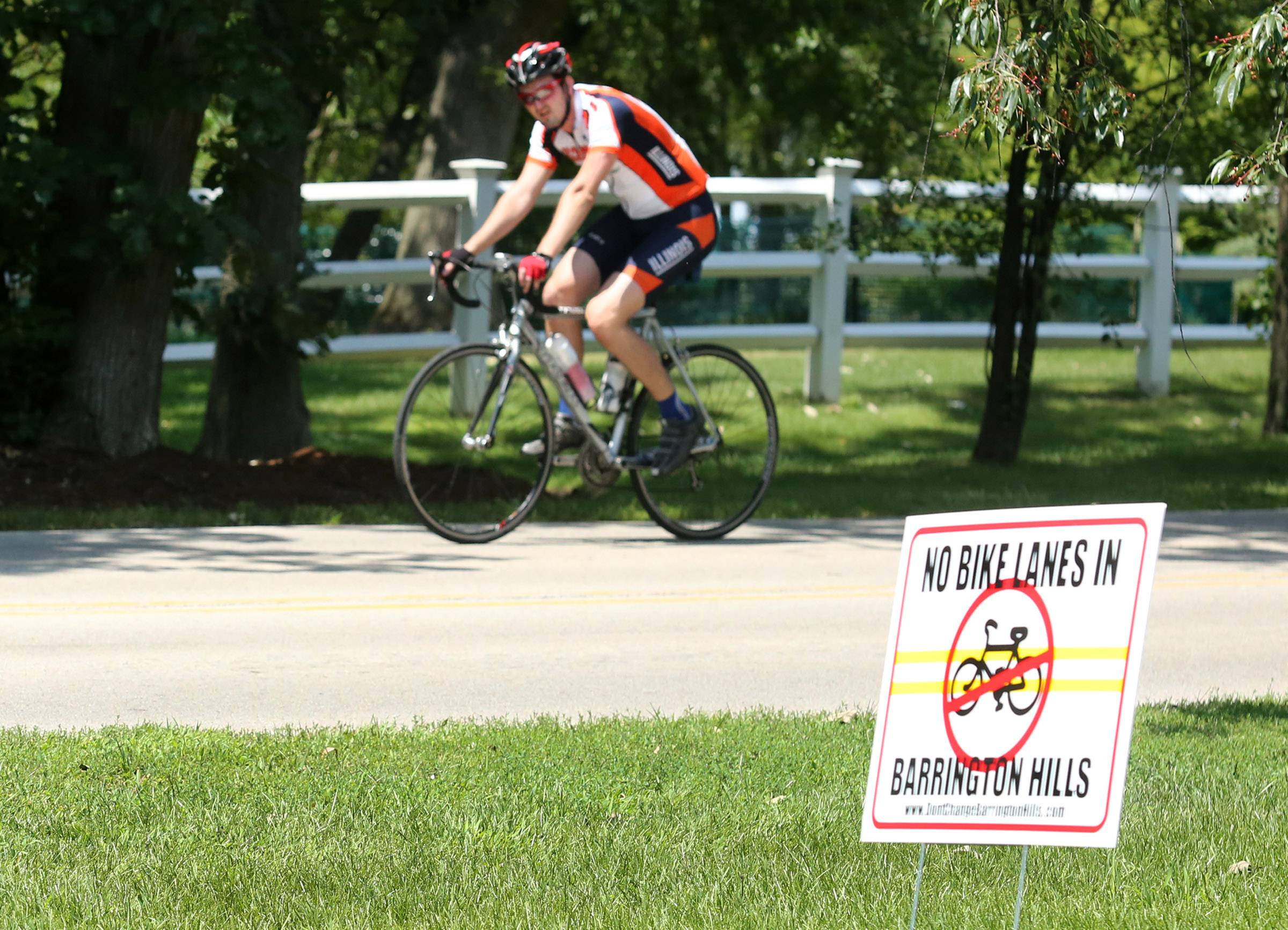 A cyclist passes an anti-bike lane yard sign earlier this month on Ridge Road in Barrington Hills.