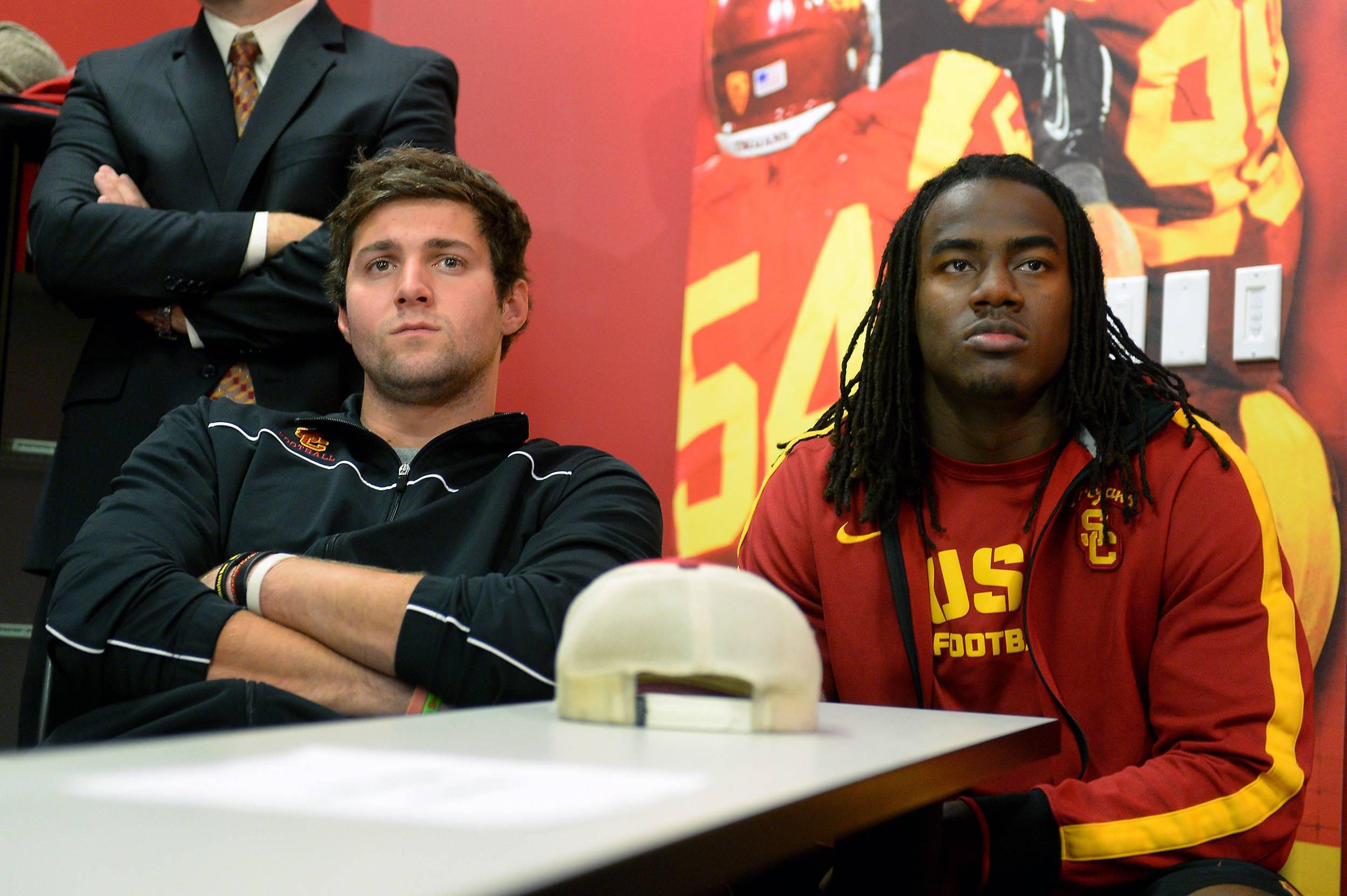 "FILE - In this Dec. 3, 2013, file photo, Southern California quarterback Cody Kessler, left, and Josh Shaw watch a news conference for USC's new football coach Steve Sarkisian in Los Angeles. Shaw has admitted to lying to school officials about how he sprained his ankles last weekend, retracting his story about jumping off a balcony to save his drowning nephew. Shaw has been suspended indefinitely from all of the Trojans' team activities after acknowledging his heroic tale was ""a complete fabrication,"" the school announced in a statement Wednesday, Aug. 27, 2014. (AP Photo/Los Angeles Daily News, Michael Owen Baker, File) NO SALES; MAGAZINES OUT; HILLS OUT, LOS ANGELES TIMES OUT; VENTURA COUNTY STAR OUT; ANTELOPE VALLEY PRESS OUT"