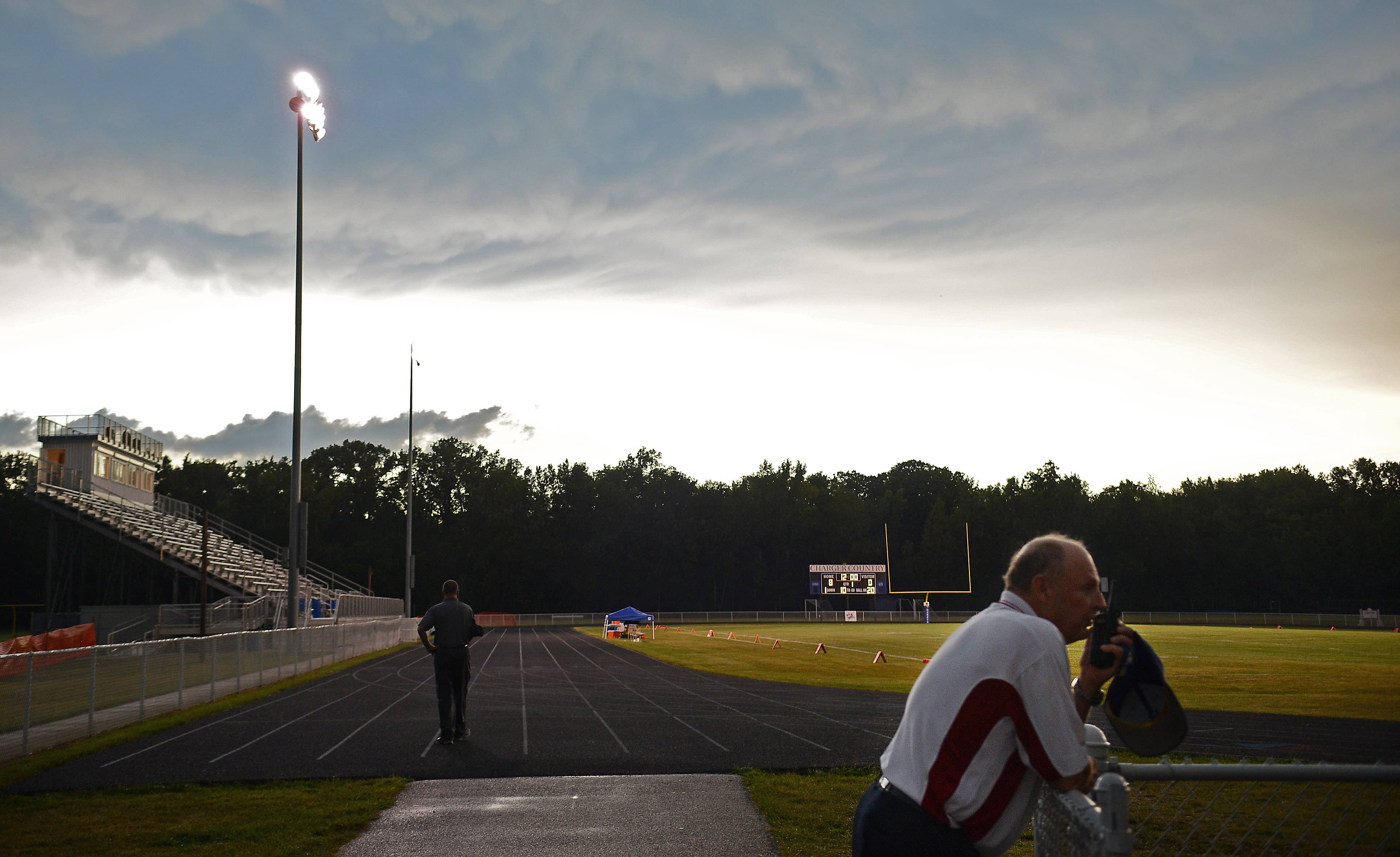 Dundee-Crown athletic director Dick Storm communicates via walkie talkie with officials as lightning delays opening night of the 2013 season.