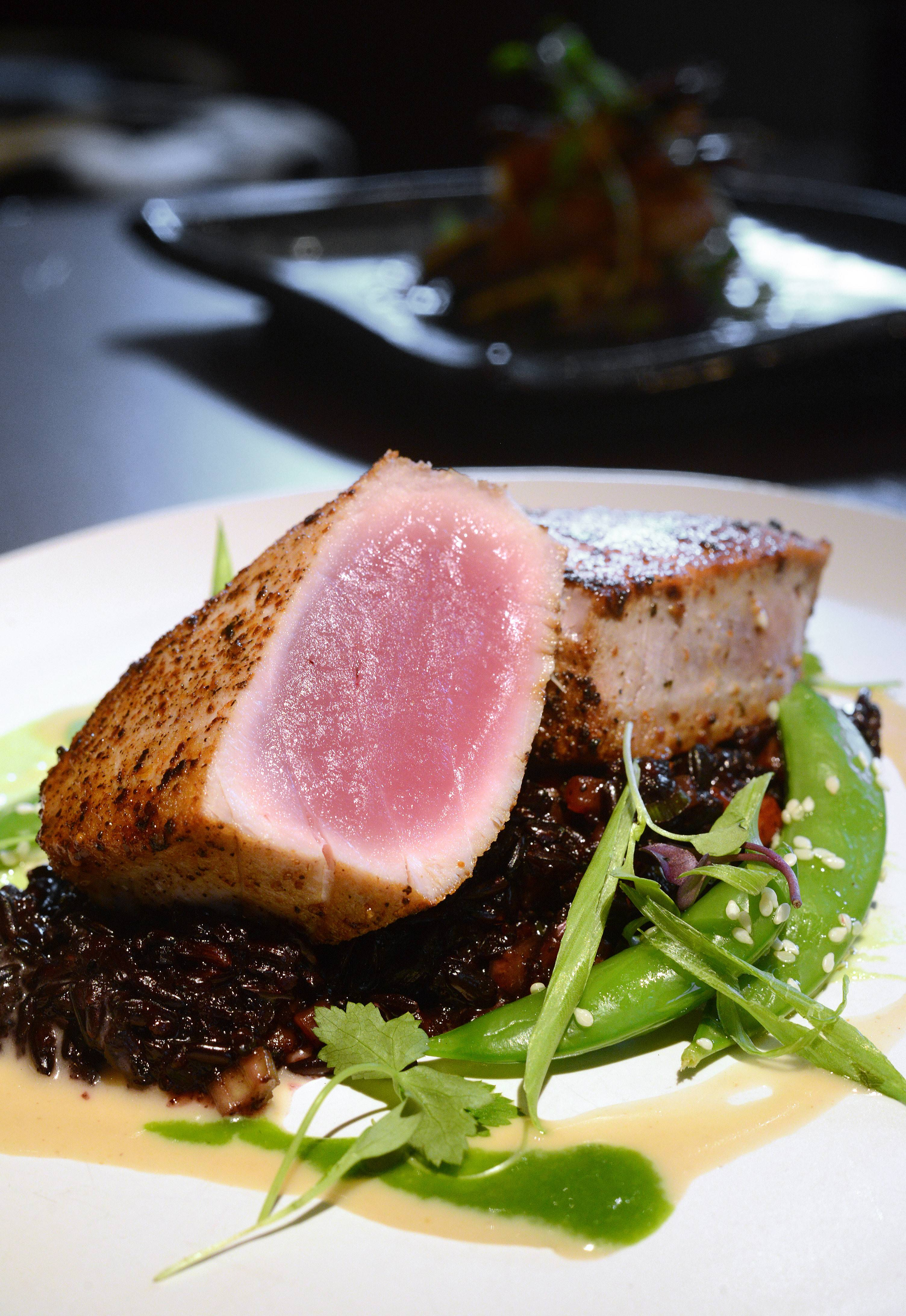Seared ahi tuna rests on a bed of sticky purple rice at Niche in Geneva. The dish is accented with coconut shellfish cream, edamame purée and honeyed snap peas.