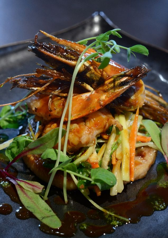 A shrimp and pork belly appetizer at Niche includes whole gulf shrimp, seared porchetta, spiced red curry, pea tendrils, shaved zucchini and scallions.