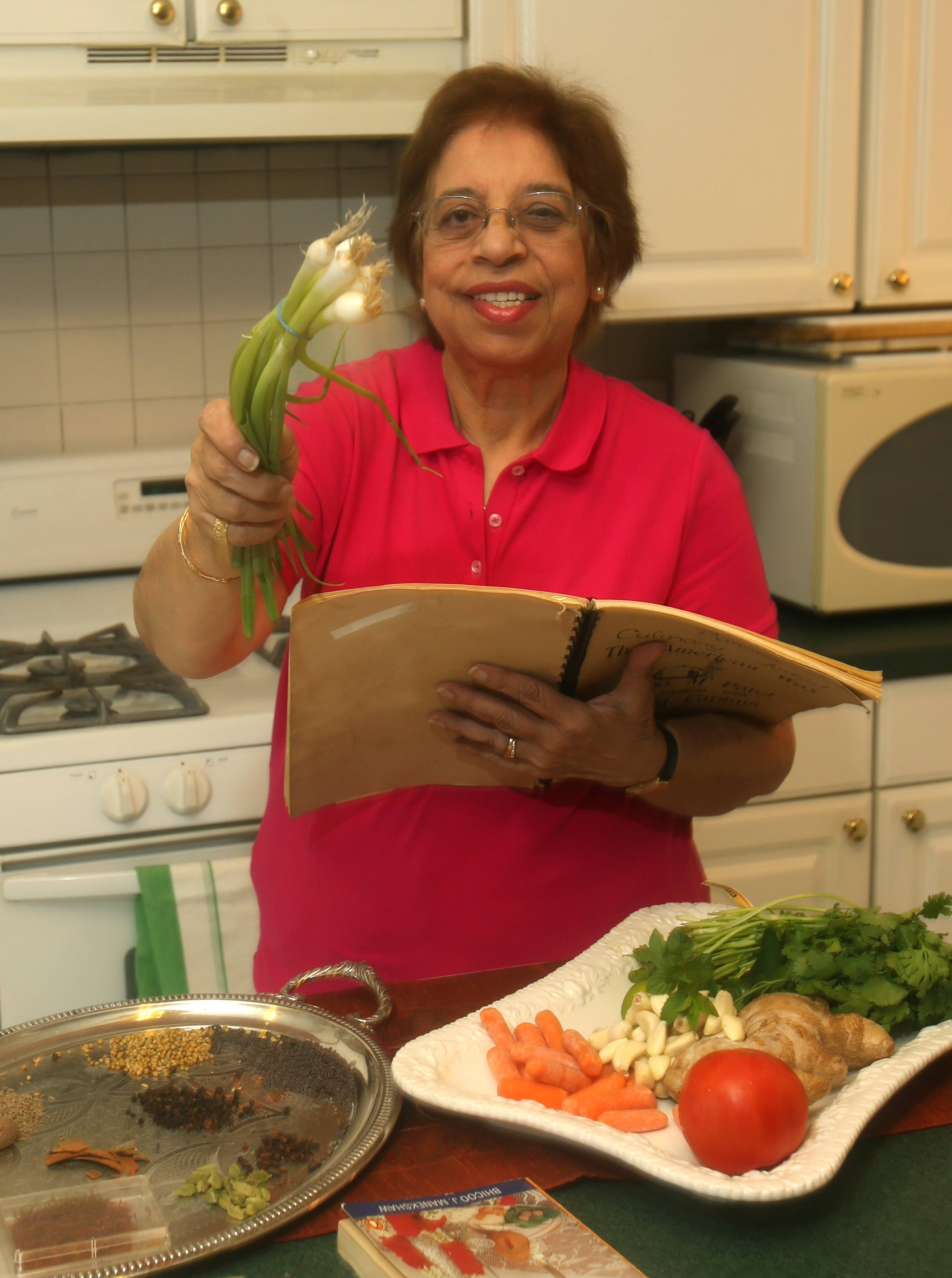 Aban Daboo of Aurora shows her favorite cooking ingredients, including fresh vegetables and spices, along with an old cookbook.