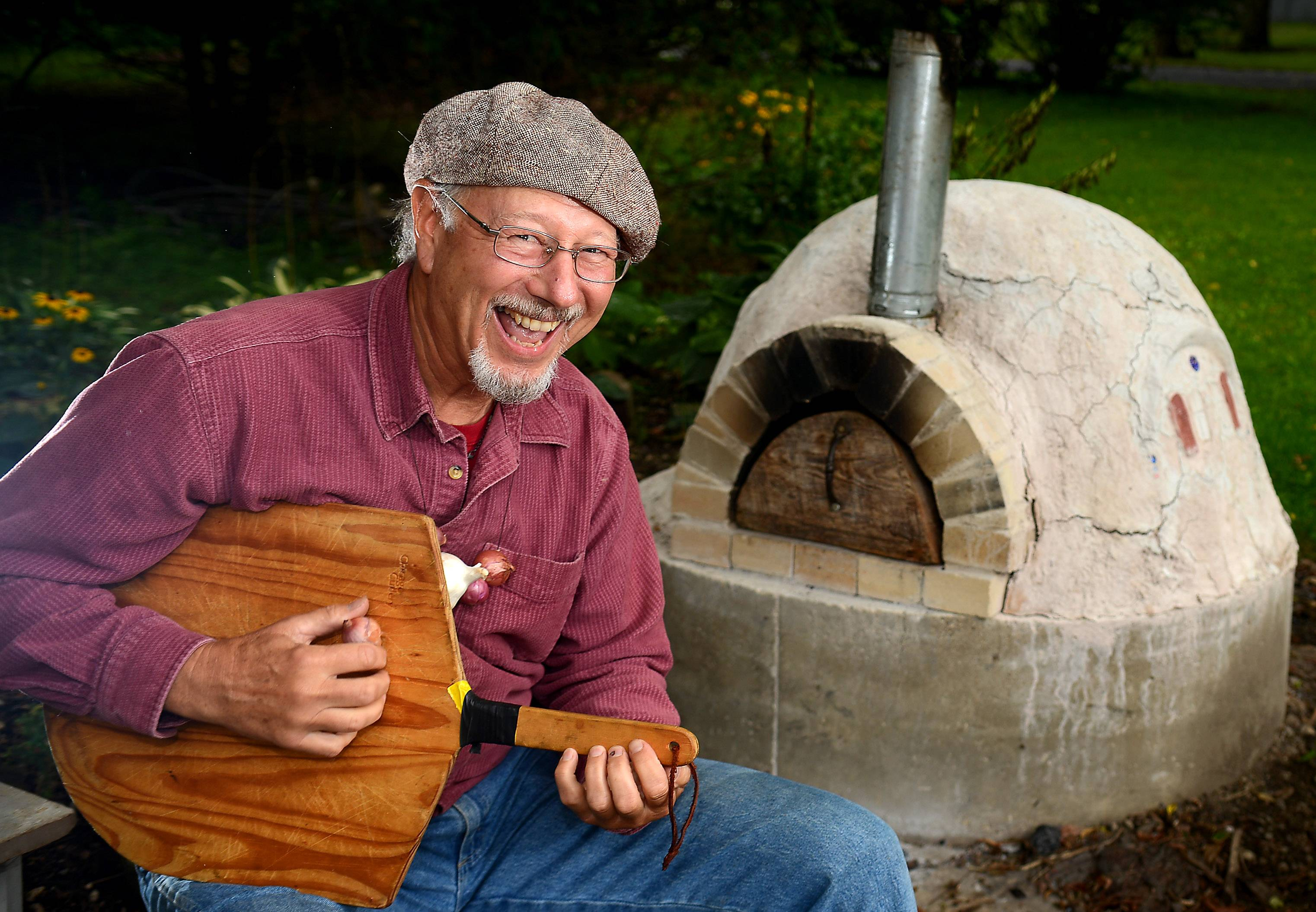 David Rench of Spring Grove plays a mean pizza paddle by his homemade clay pizza oven. His necklace of shallots and garlic shows his appreciation of the ingredients and may or may not help ward off vampires.