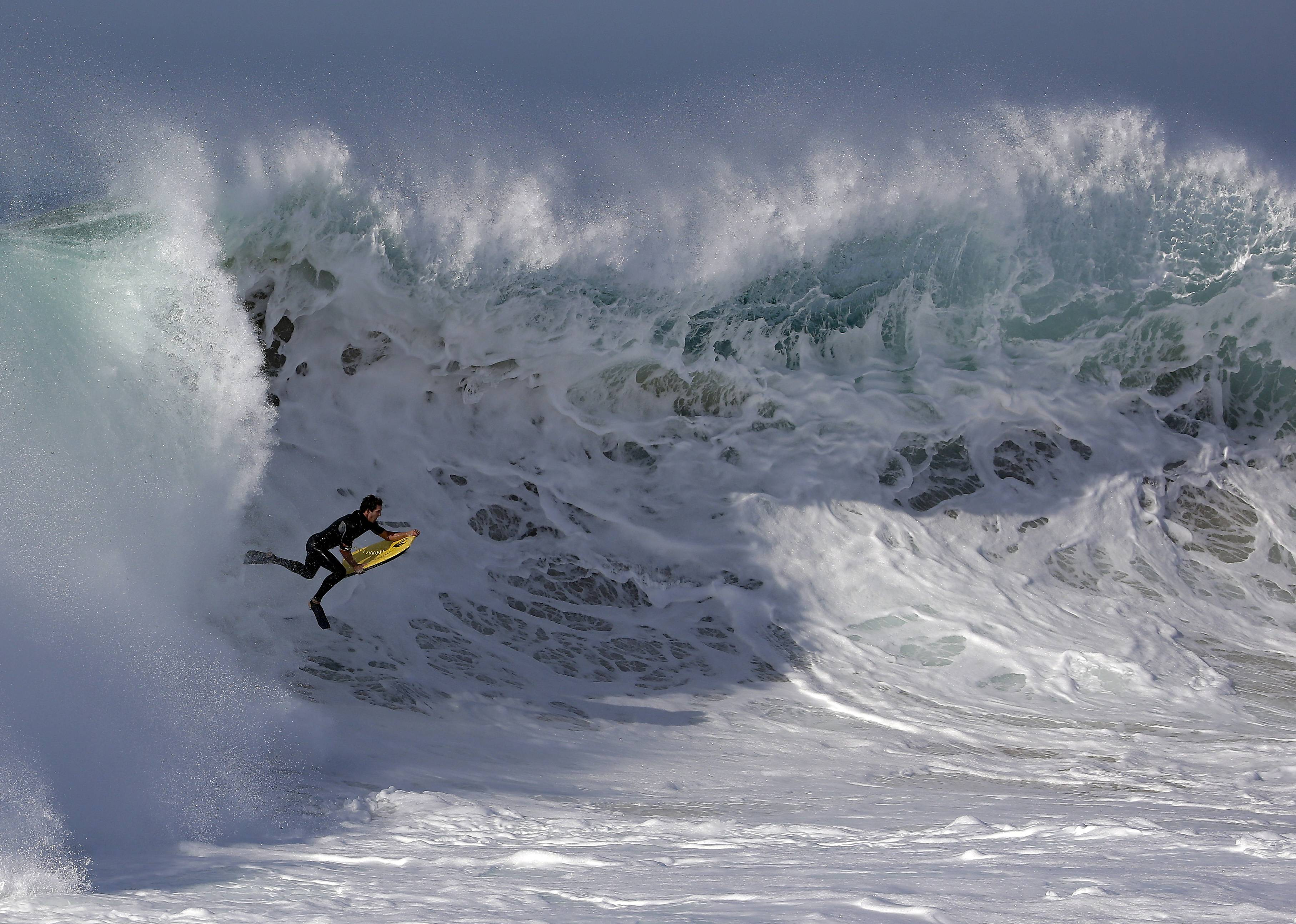 A bogieboarder rides a wave in Newport Beach, Calif., Wednesday, when Southern California beachgoers experienced much higher than normal surf, brought on by Hurricane Marie spinning off the coast of Mexico.