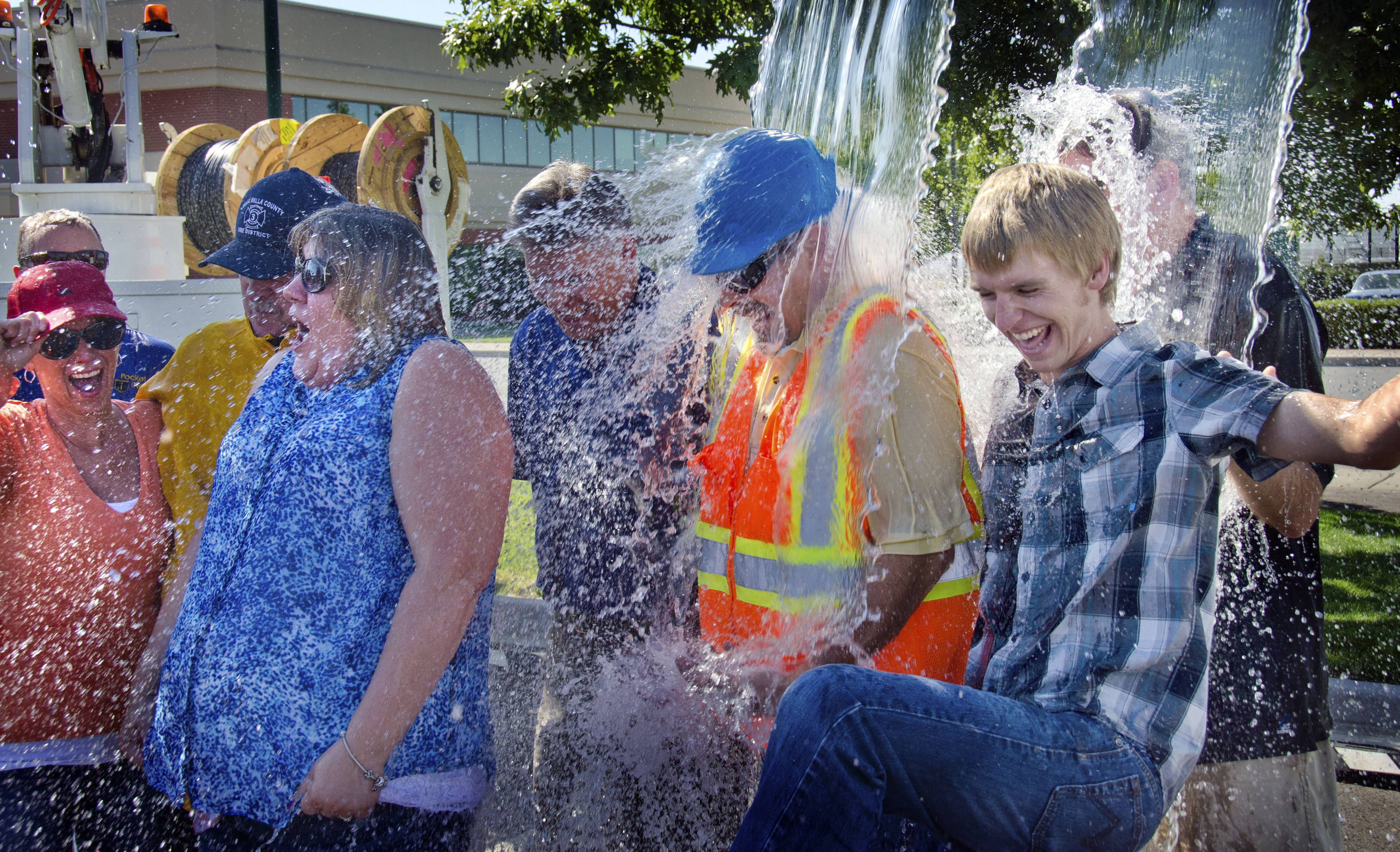 In this photo taken on Tuesday, Ten Pocket iNet corporation employees take the ice bucket challenge at the Walla Walla Regional Airport in Walla Walla, Wash., to benefit ALS research.