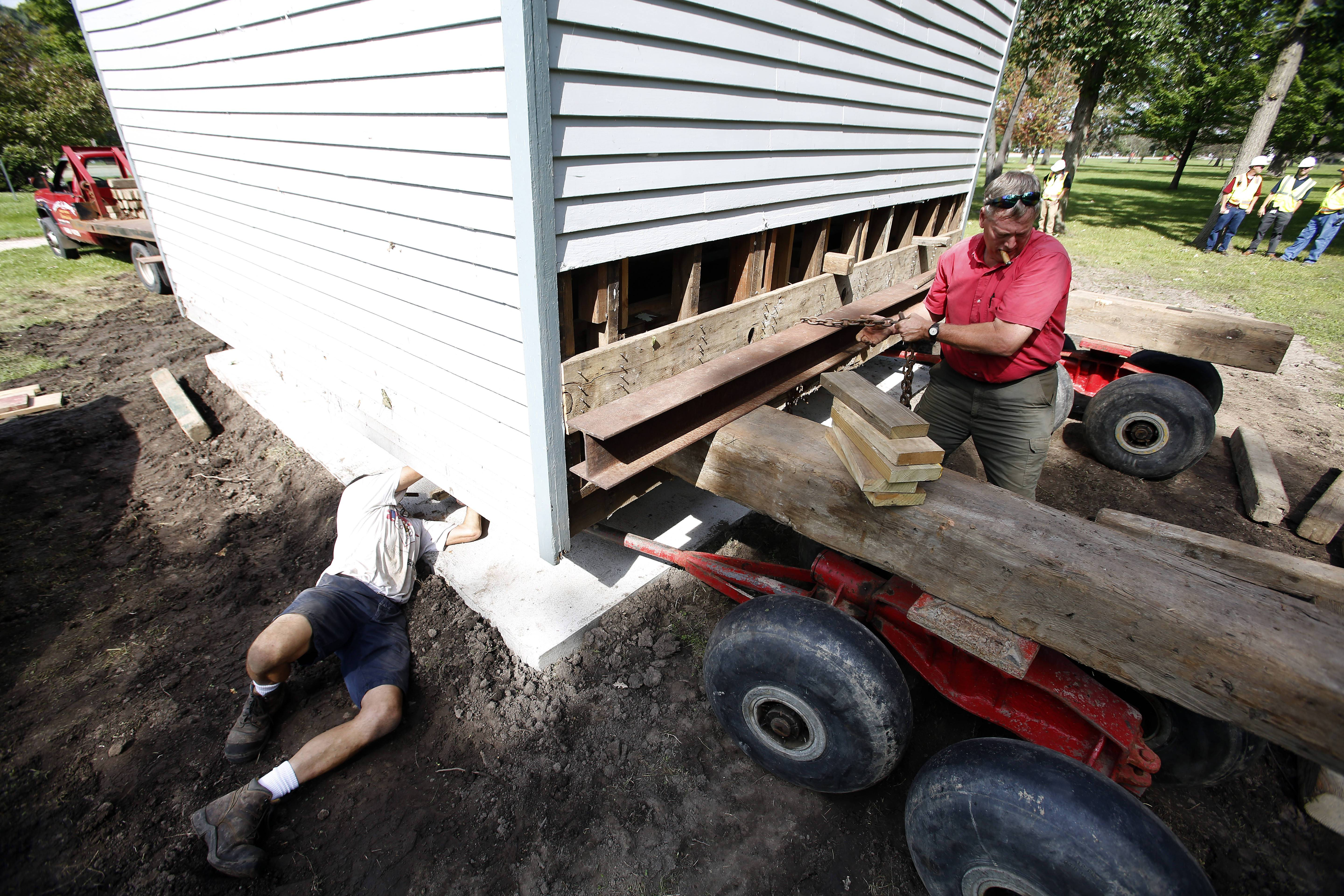 Brian Heinlein, left, and Gary Muehlfelt, prepare to lower the Jones Law Office building to its new location Wednesday in Langum Park along Route 25 in St. Charles.