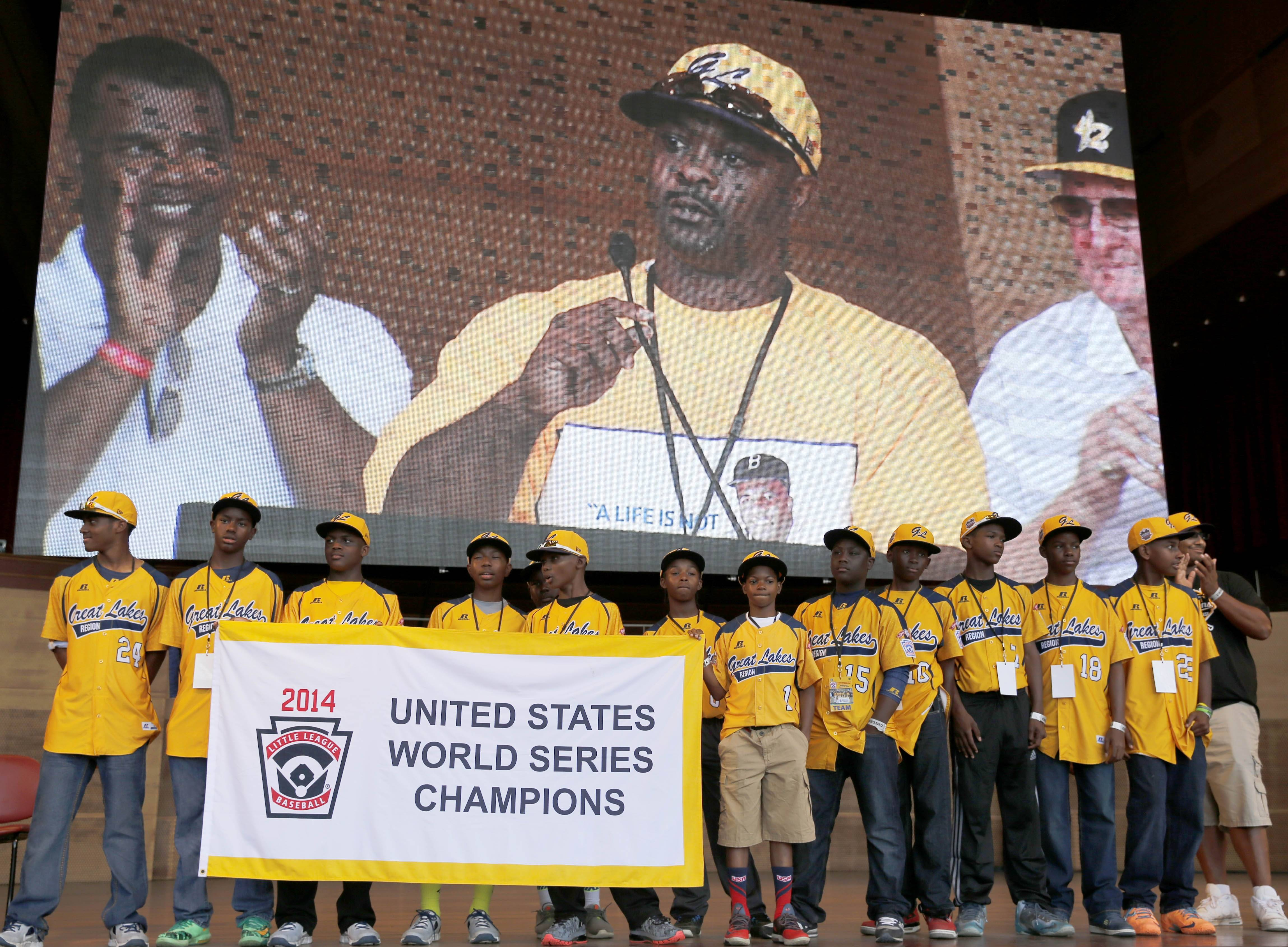 Members of the Jackie Robinson West All Stars Little League Baseball team participate in a rally and listen to manager Darold Butler on the big screen as they celebrate the team's U.S. Little League Championship Wednesday at Chicago's Millennium Park.