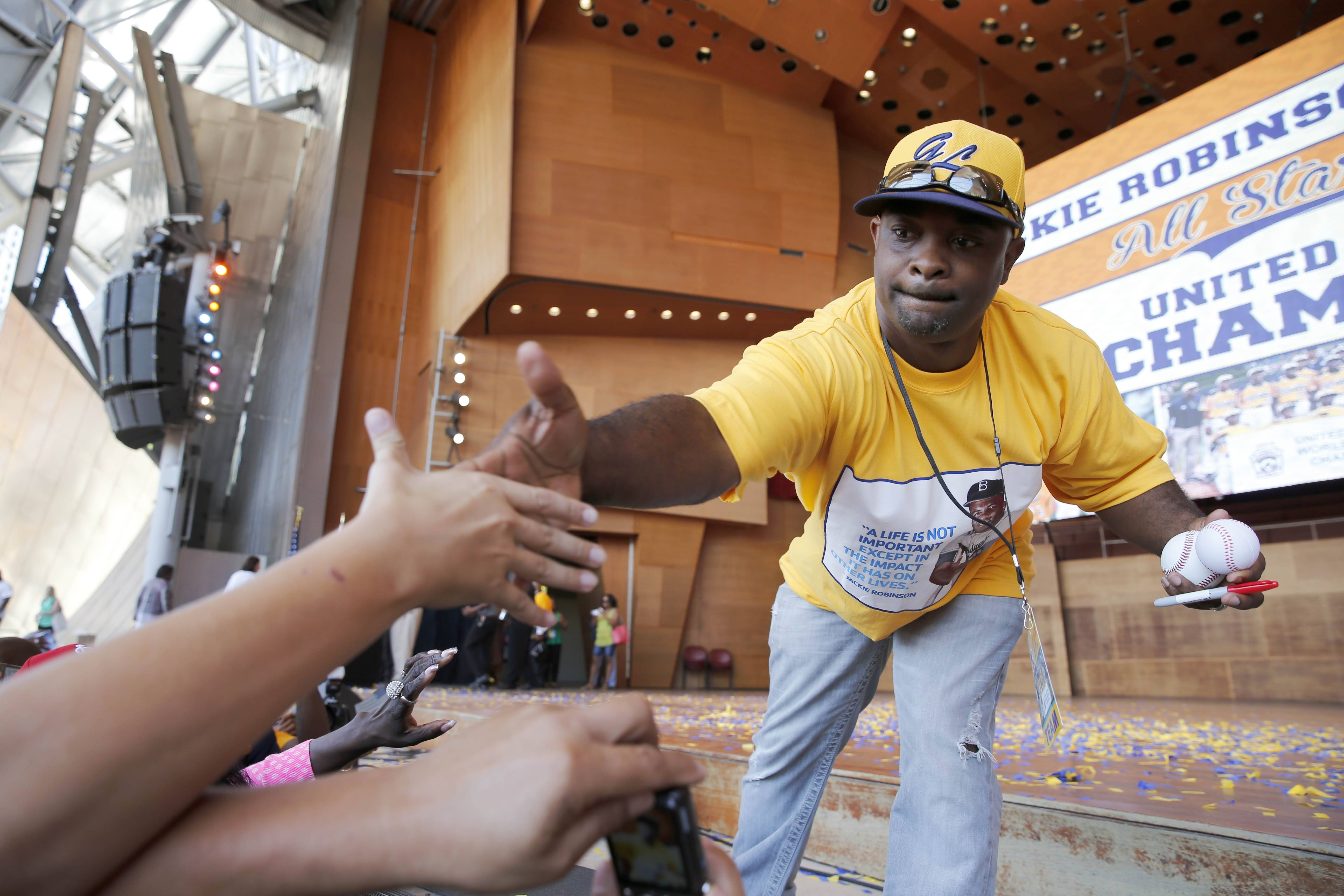 Jackie Robinson West All Stars Little League Baseball team manager Darold Butler shakes the hand of a fan as his team participate in a rally to celebrate the team's U.S. Little League Championship Wednesday at Chicago's Millennium Park.