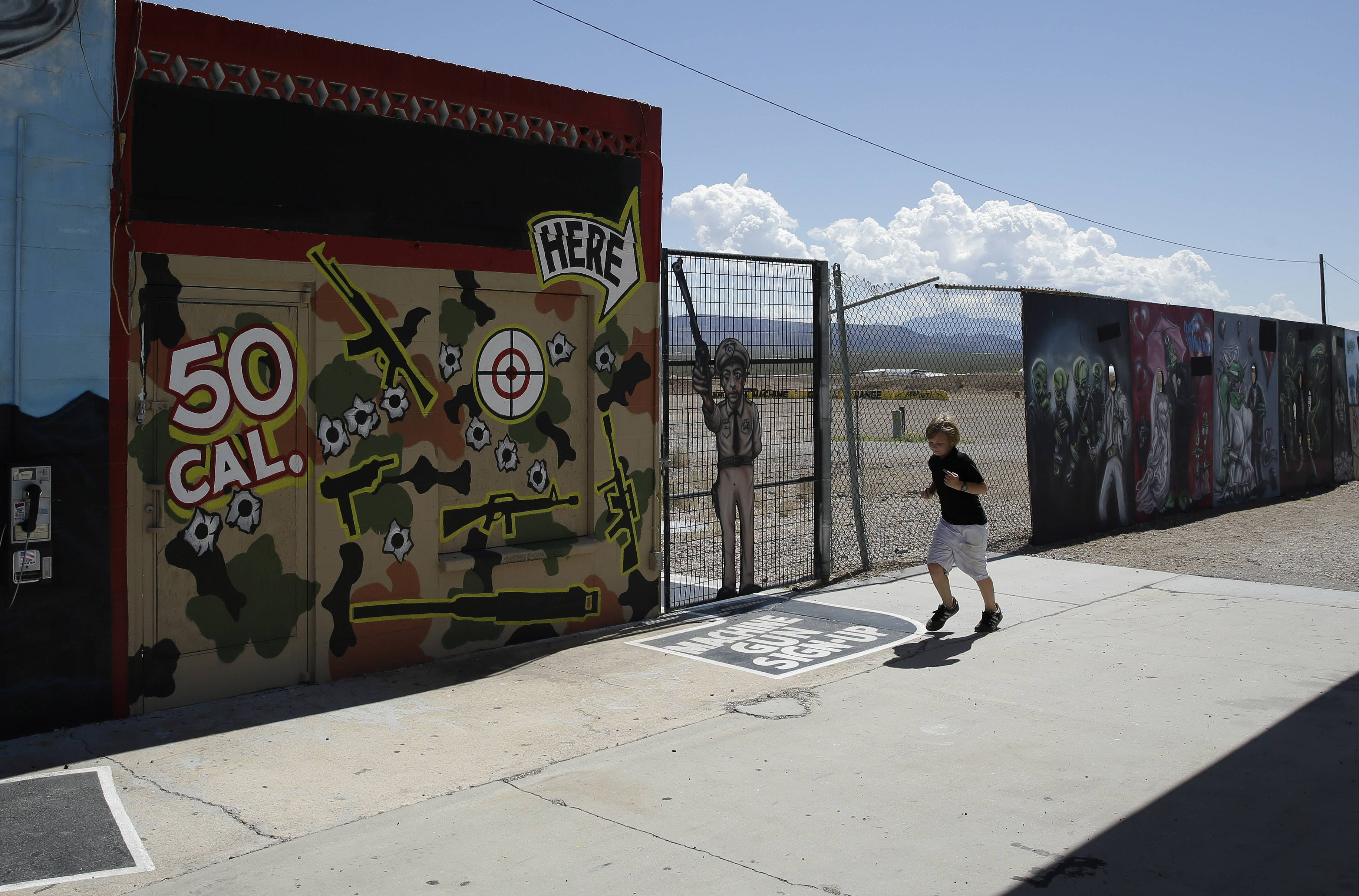A young person runs by the Last Stop outdoor shooting range Wednesday, Aug. 27, 2014, in White Hills, Ariz. Gun range instructor Charles Vacca was accidentally killed Monday, Aug. 25, 2014 at the range by a 9-year-old with an Uzi submachine gun.