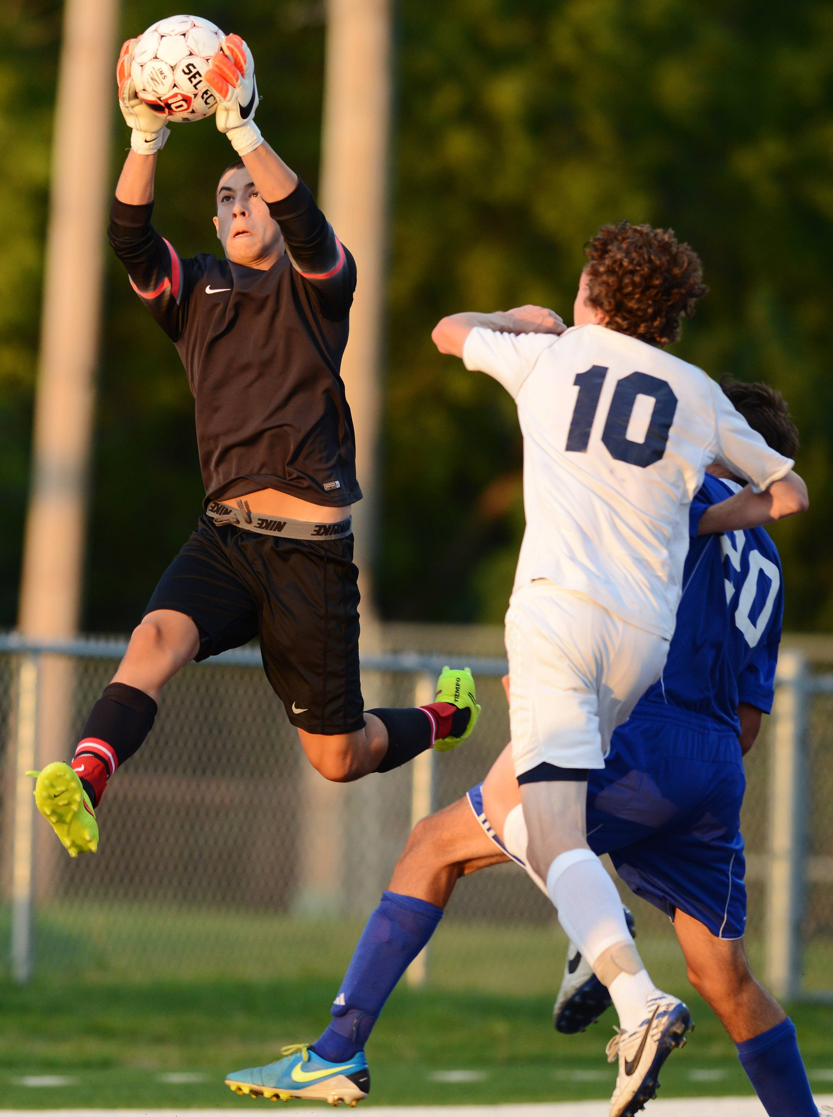 Lake Zurich goalkeeper George Maroudas leaps to take control of the ball in front of St. Viator's Aiden Williams following a Lions corner kick during Wednesday's game.
