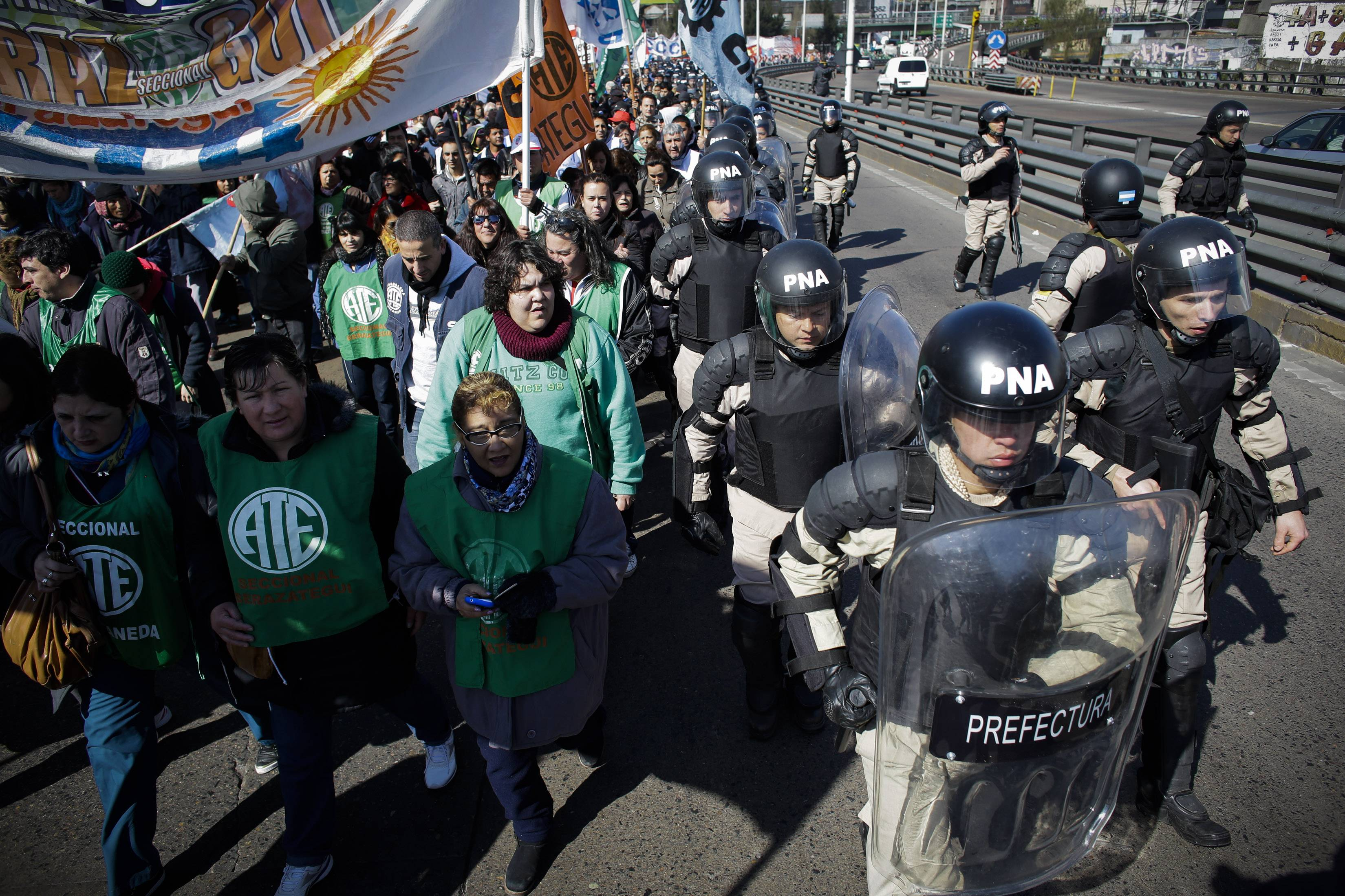 Riot police cordon off protesters partially blocking one of Buenos Aires' main access routes over the Riachuelo River in Argentina. CTA, a union umbrella group that opposes the government, started a 36-hour strike to demand more jobs, better salaries and tax cuts on salaries.
