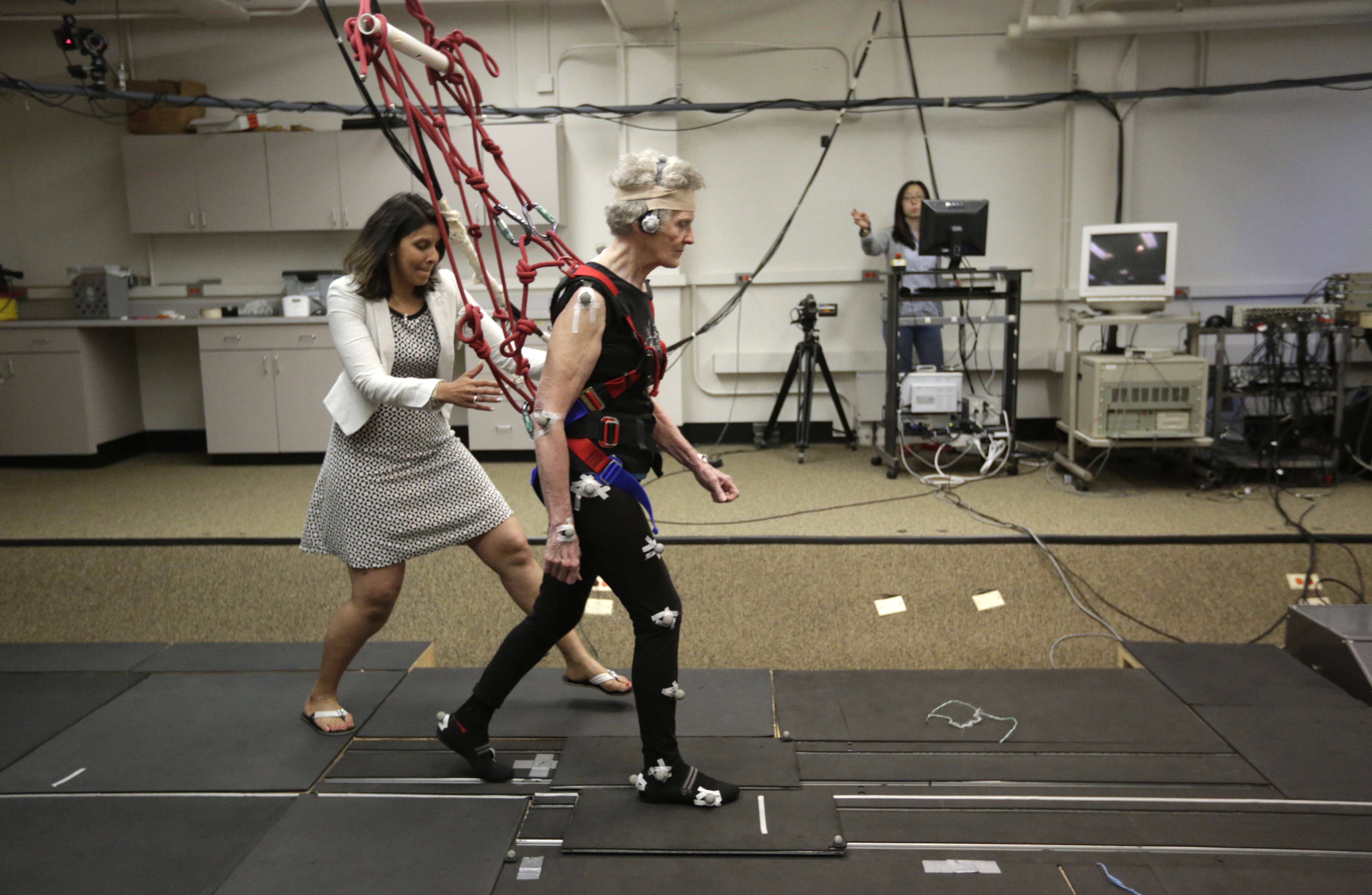 University of Illinois-Chicago physical therapy assistant professor Tanvi Bhatt, left, walks alongside Mary Kaye, 81, as she demonstrates a treadmill balance session. Kaye, supported by a safety harness, walks on a lab-built walkway that causes people to unexpectedly trip and can teach them quickly how to catch themselves and avoid falling.