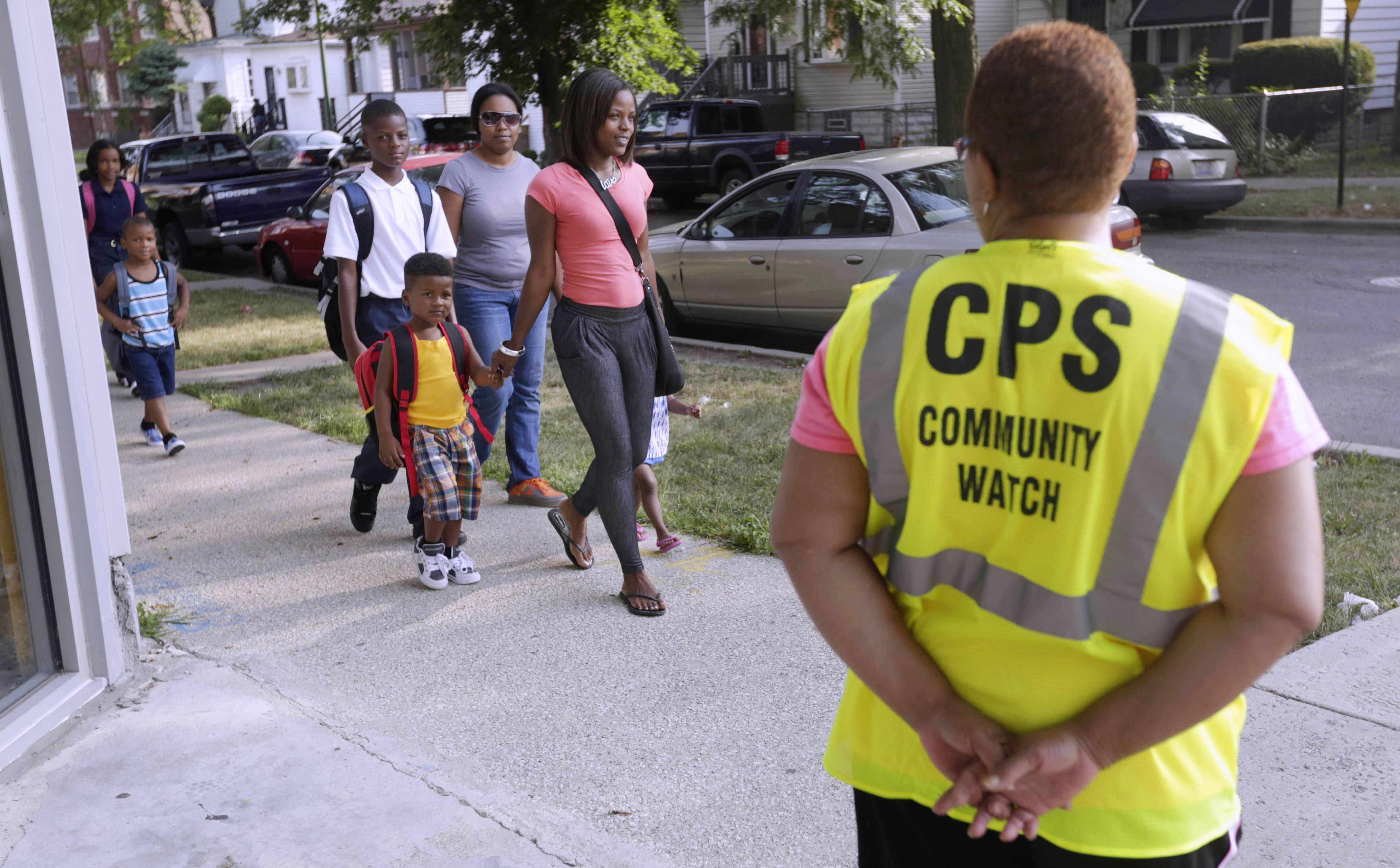 Safety guard Renee Green watches as parents walk with their children along a Safe Passage route on the first day of school last year in Chicago.