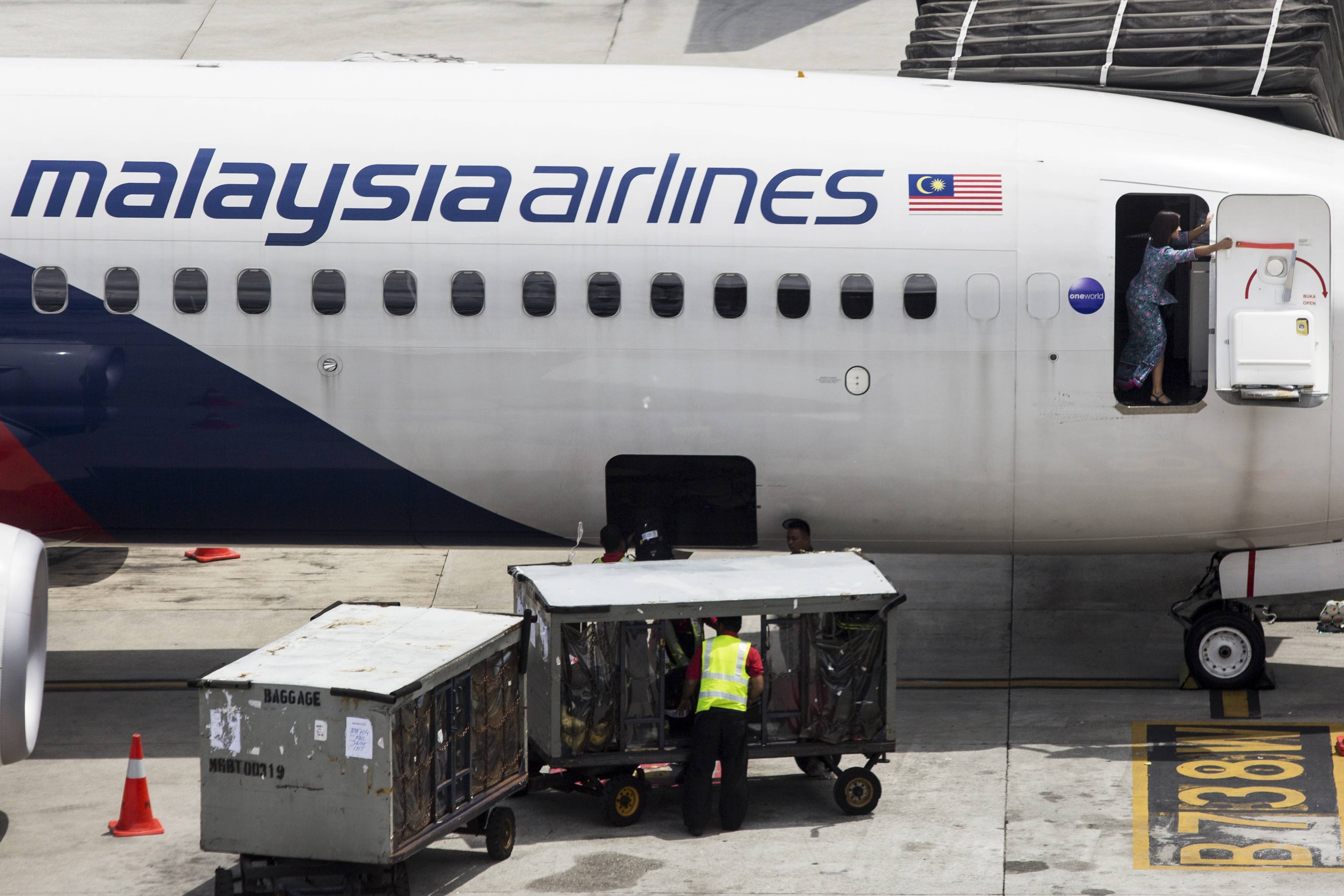 A flight attendant reaches out to close the door of an aircraft operated by Malaysian Airline System Bhd. (MAS) at Kuala Lumpur International Airport (KLIA) in Sepang, Malaysia. The airlines which lost a plane to a missile in Ukraine while another remains missing for months, reported a sixth quarter of losses as its majority owner considers a restructuring plan.
