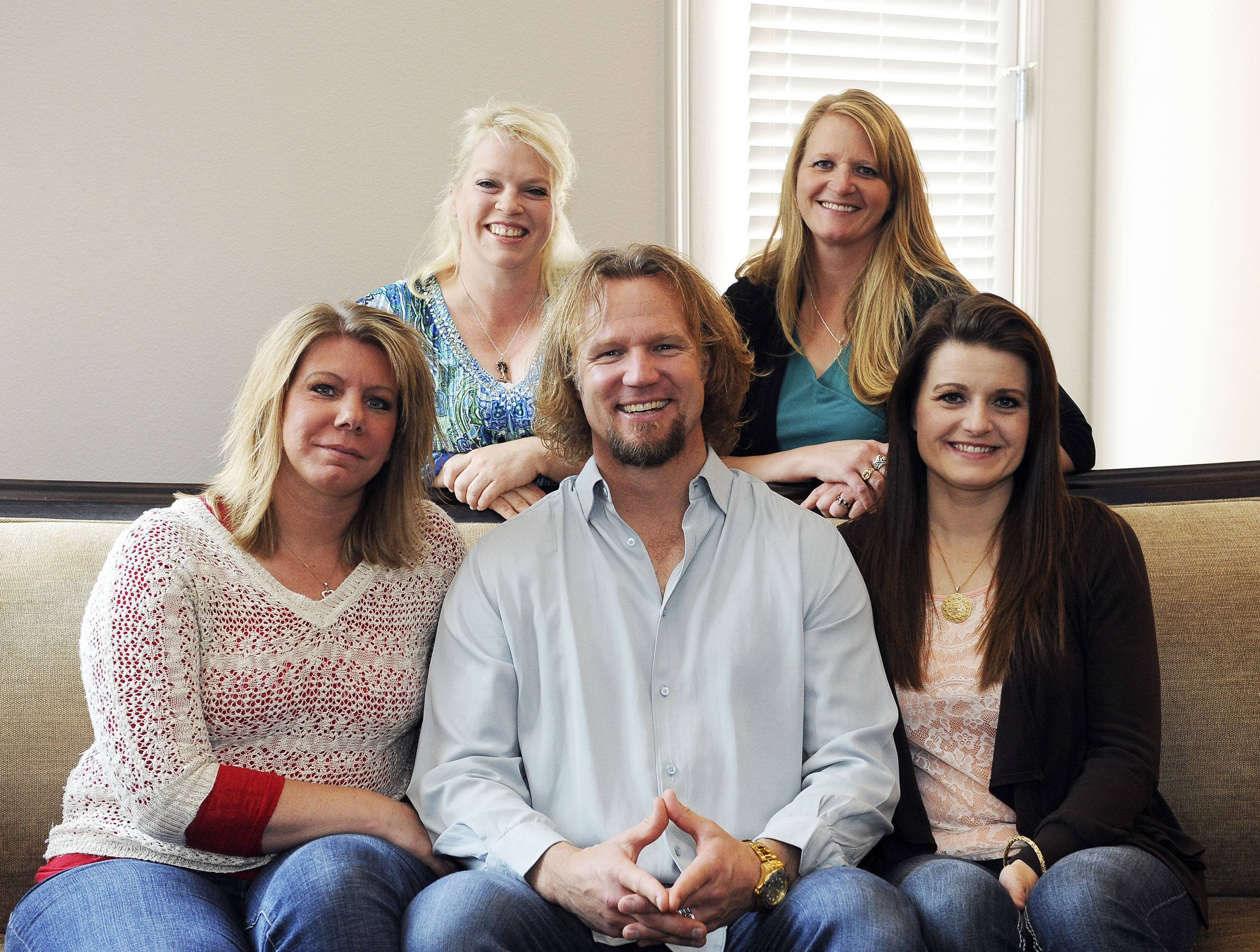 "Kody Brown poses with his wives at one of their homes in Las Vegas. A federal judge in Utah has issued a final ruling that strikes down parts of the state's anti-polygamy law, in a lawsuit filed by a family that appears on the TV show ""Sister Wives."" Kody Brown and his four wives sued Utah in 2011 after a county prosecutor threatened to charge them under the state's bigamy law."