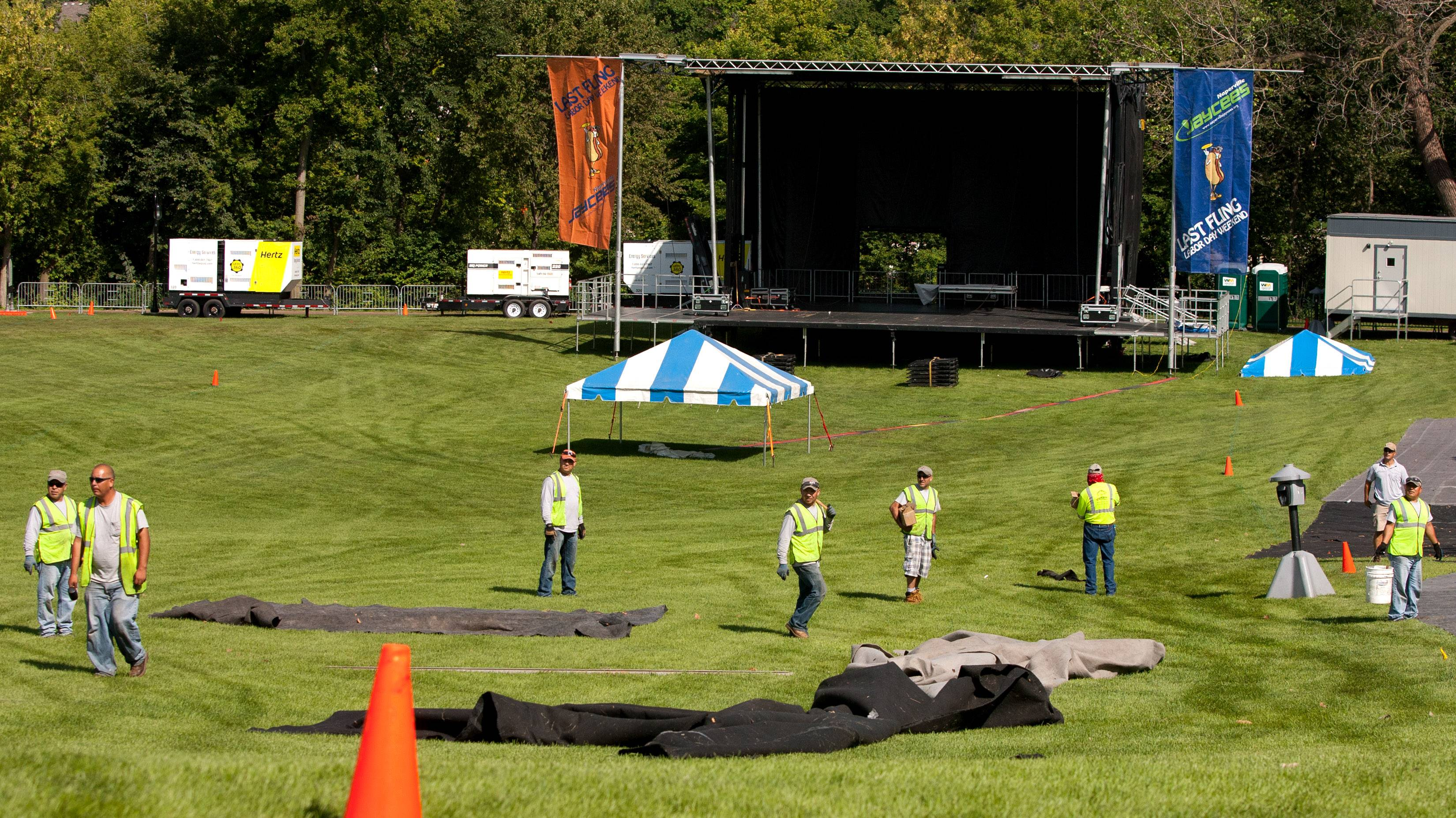 Workers continue working Thursday near the Main Stage area where bands such as O.A.R. and Smash Mouth will perform this weekend as part of Naperville's Last Fling celebration.