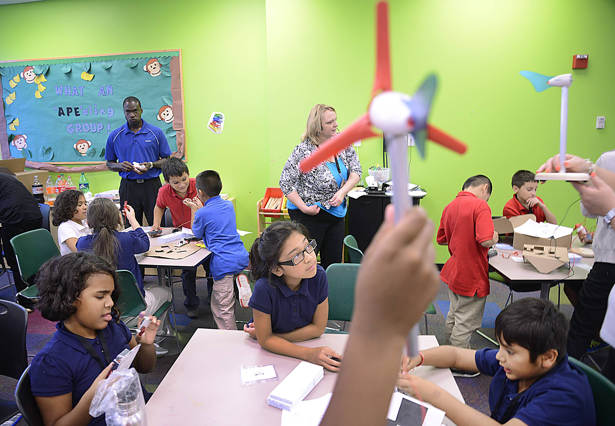 A miniature wind turbine is held in the air as students, including Carmen Rivera, left, Anahi Uribe and Isaac Garcia, all 9, start to build their project Tuesday at the Boys & Girls Club of Elgin. Siemens USA brought its STEM (Science, Technology, Engineering and Math) program to club members to teach them about clean energy and the possibility of technical careers.