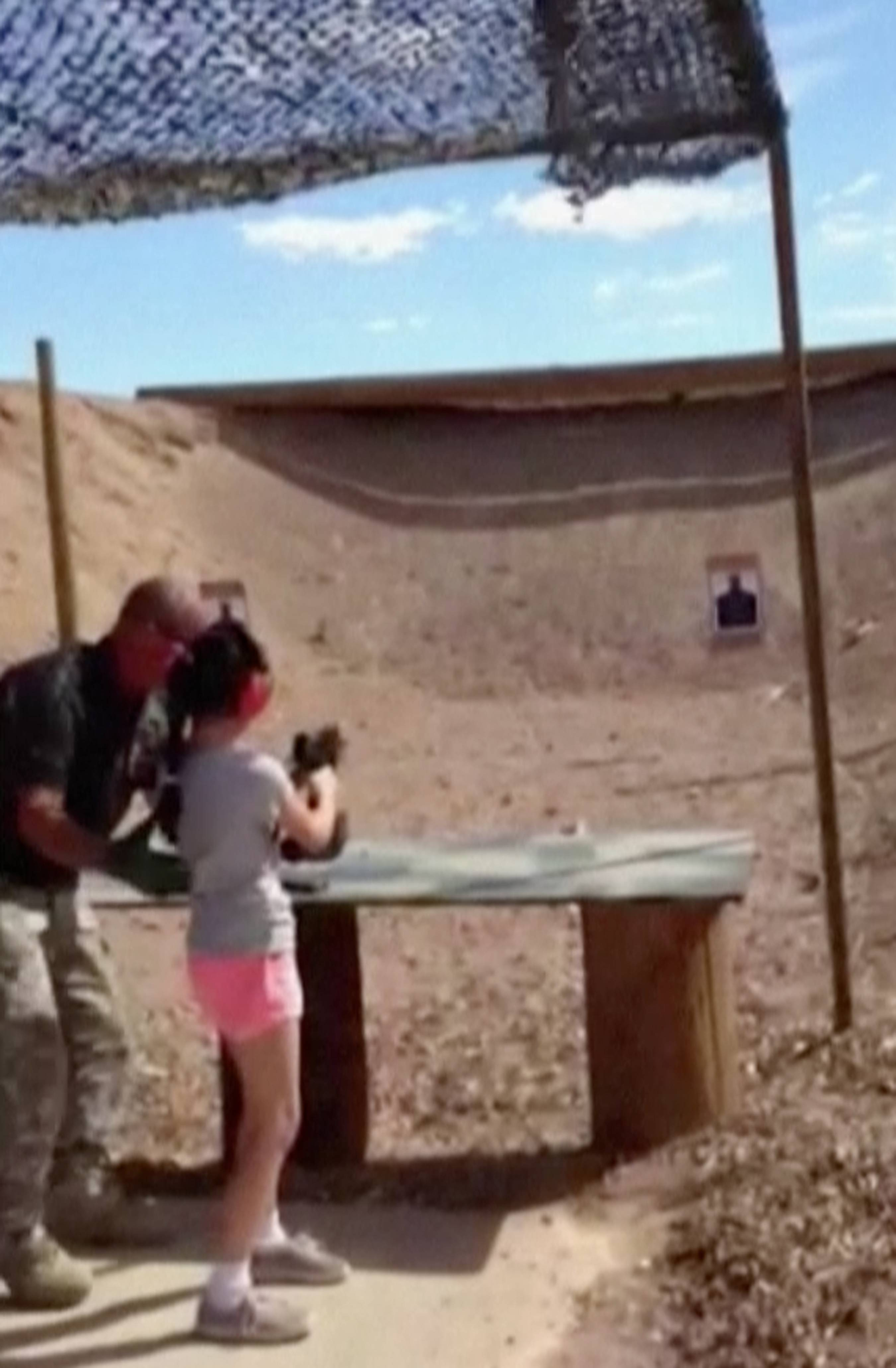 In this image made from video, firing-range instructor Charles Vacca, left, shows a 9-year old girl how to use an Uzi. Vacca, 39, was standing next to the girl on Monday at the Last Stop range in Arizona, south of Las Vegas, when the girl squeezed the trigger, causing the Uzi to recoil upward and shoot Vacca in the head.