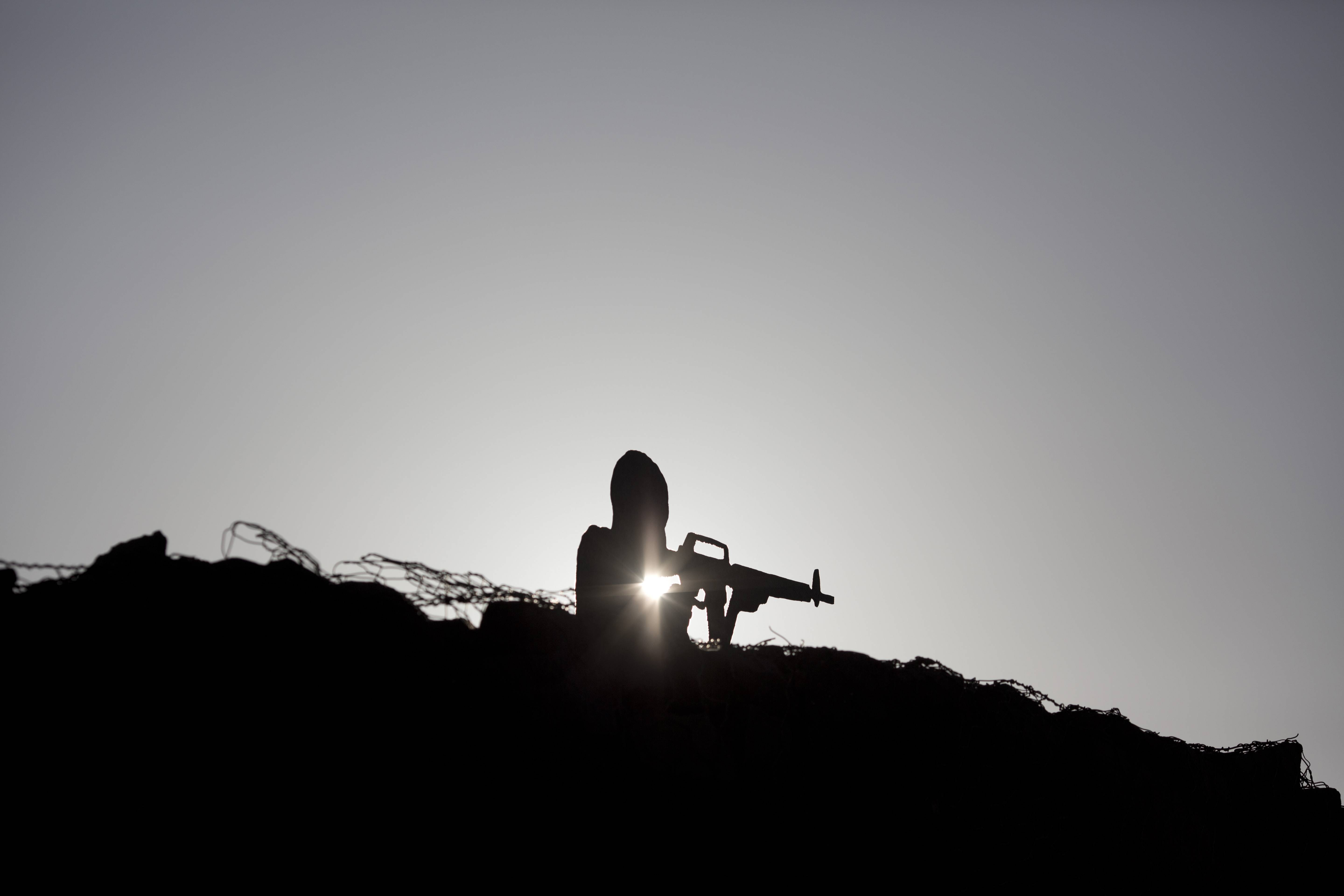 A metal board in the shape of a gunman sits on an old bunker at an observation point on Mt. Bental in the Israeli-controlled Golan Heights, overlooking the border with Syria Syria's Quneitra province, Thursday. From the Israeli side of the de facto border, large clouds of smoke could be seen, as gunfire and explosions sounded in the distance. Israeli soldiers observed the fighting.