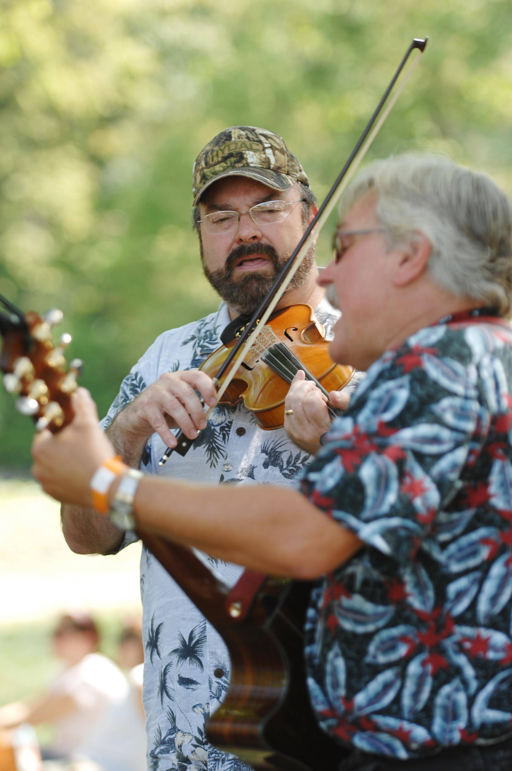 Ray Henaughan plays the fiddle and Dave Simpson of St. Charles plays guitar in an impromptu jam by the Fox River at the 36th Annual Fox Valley Folk Music and Storytelling Festival.