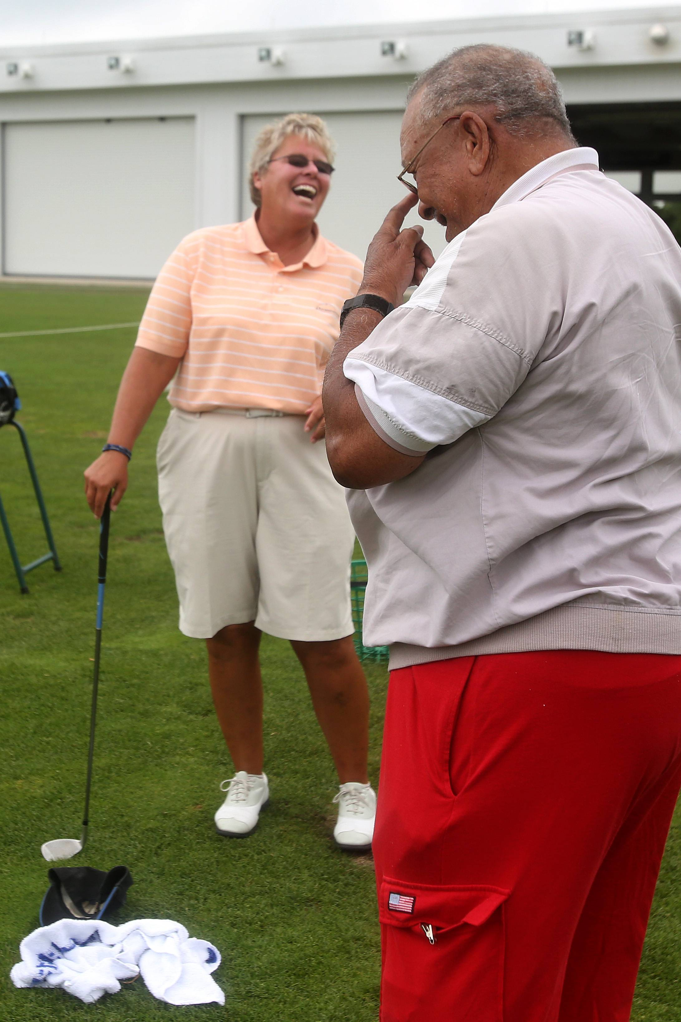 Kathy Williams, left, of RevelationGolf shares a laugh with Edward Tipton, right, at a monthly golf clinic for veterans with disabilities.