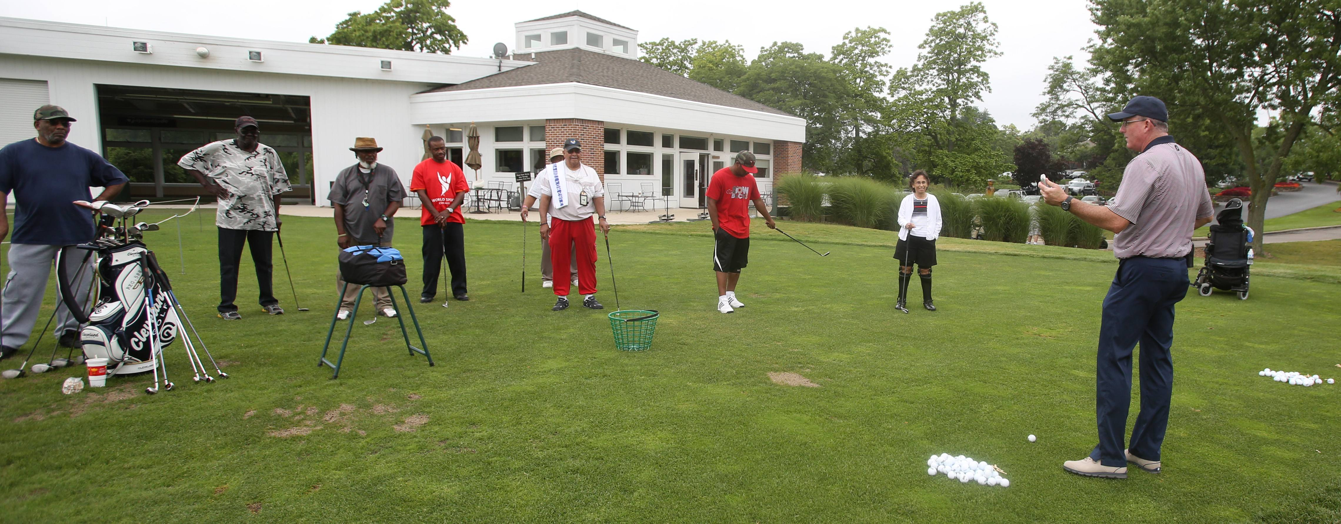 Cantigny Golf pro Patrick Lynch reviews irons technique during a clinic for veterans with physical disabilities and PTSD.