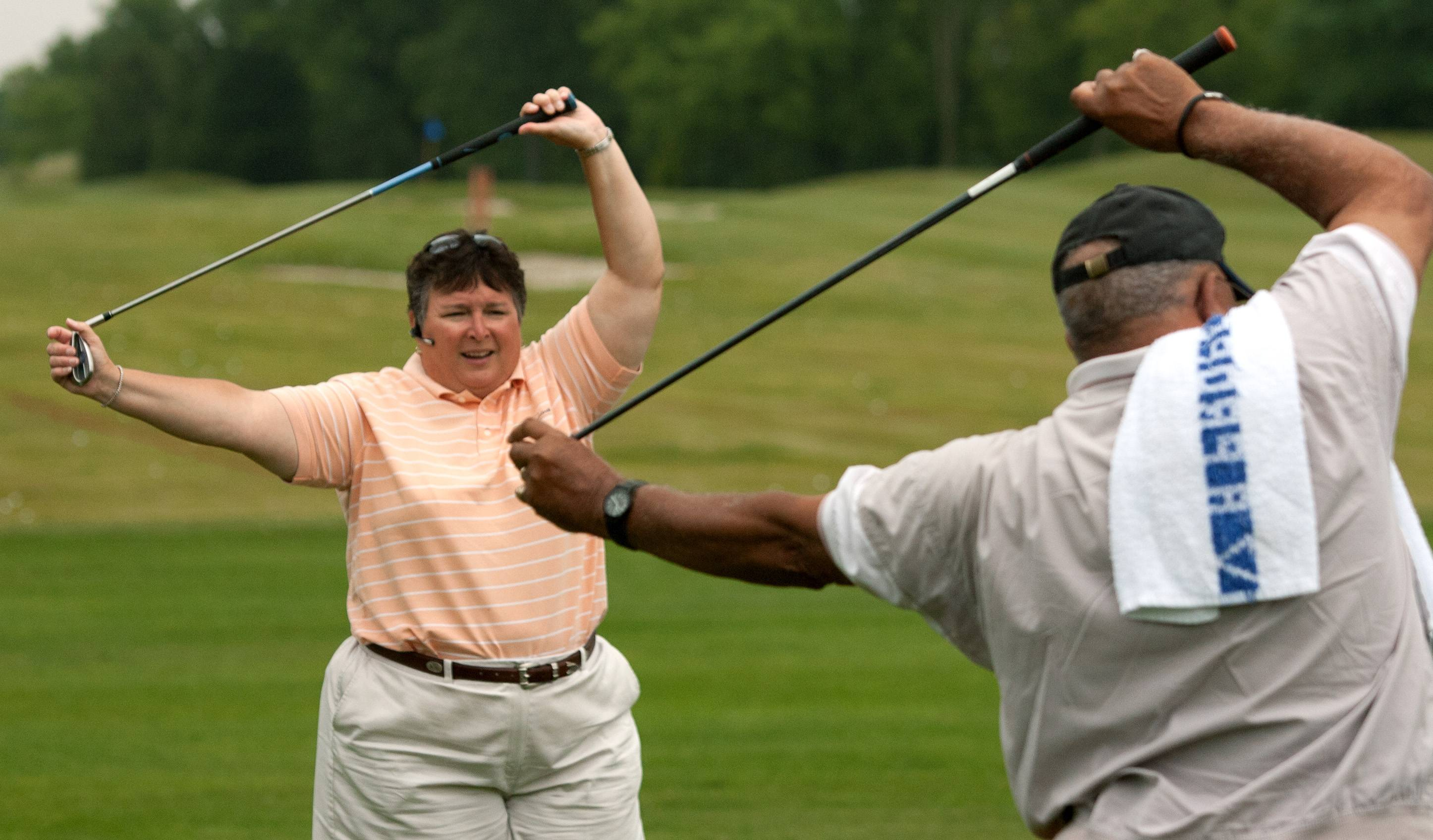 Donna Strum, left, executive director of RevelationGolf, leads stretching exercises at the beginning of a golf clinic for veterans with disabilities.