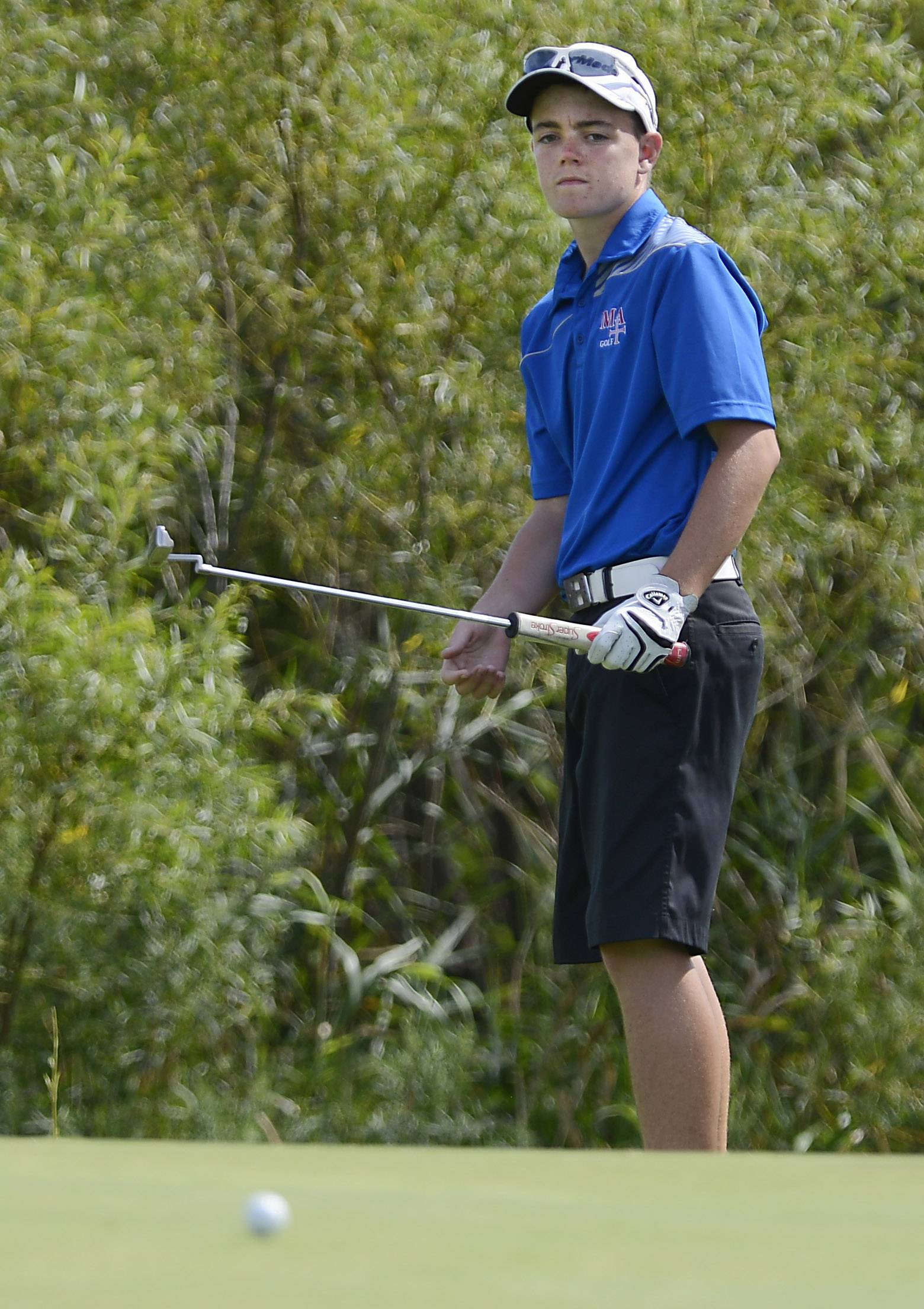 Marmion Academy's Nicholas Huggins watches his putt Thursday at the Geneva boys golf invitational at Mill Creek Golf Club.