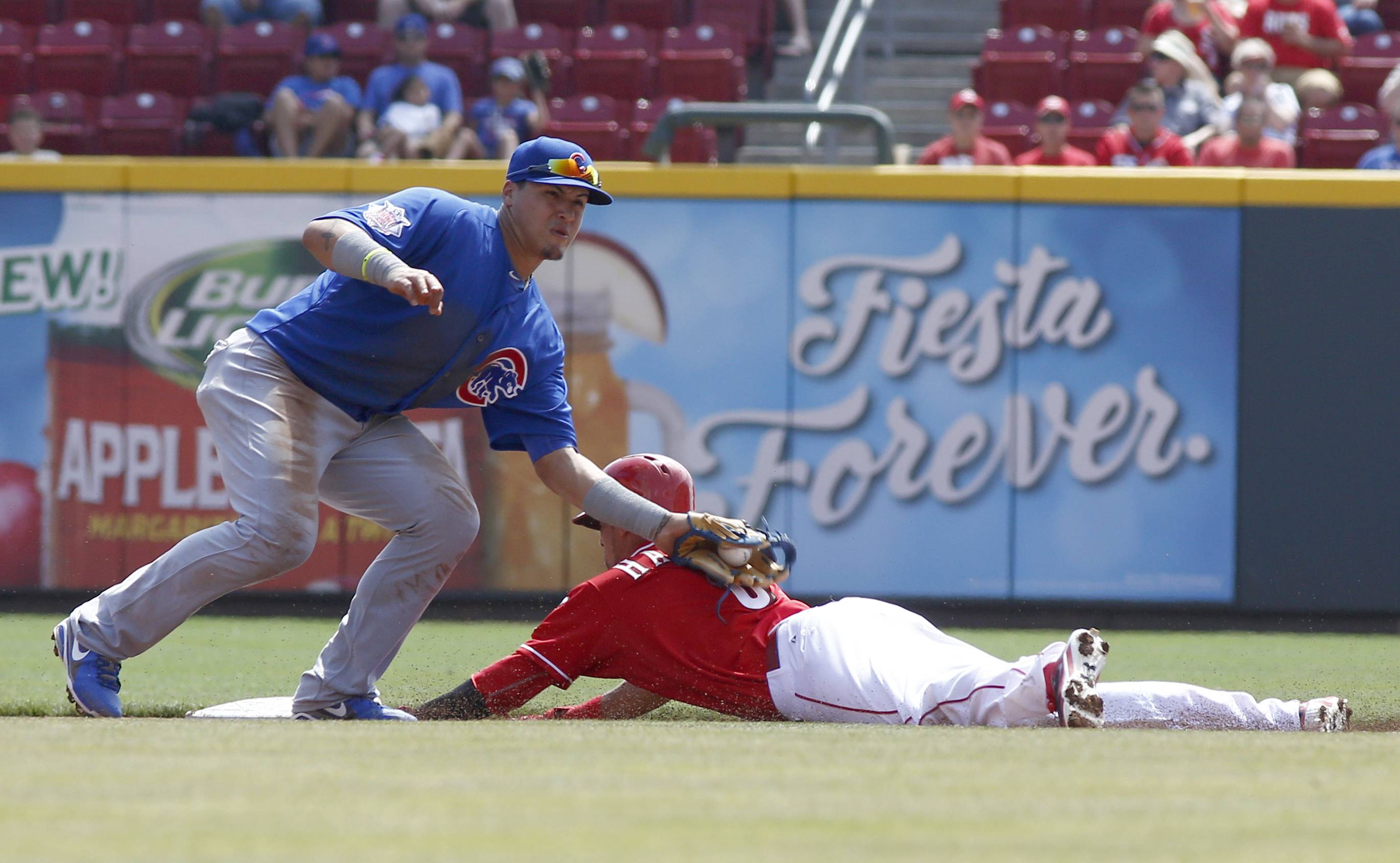Cincinnati Reds' Billy Hamilton, right, steals second base under Chicago Cubs second baseman Javier Baez, left, in the first inning of a baseball game, Thursday, Aug. 28, 2014, in Cincinnati.