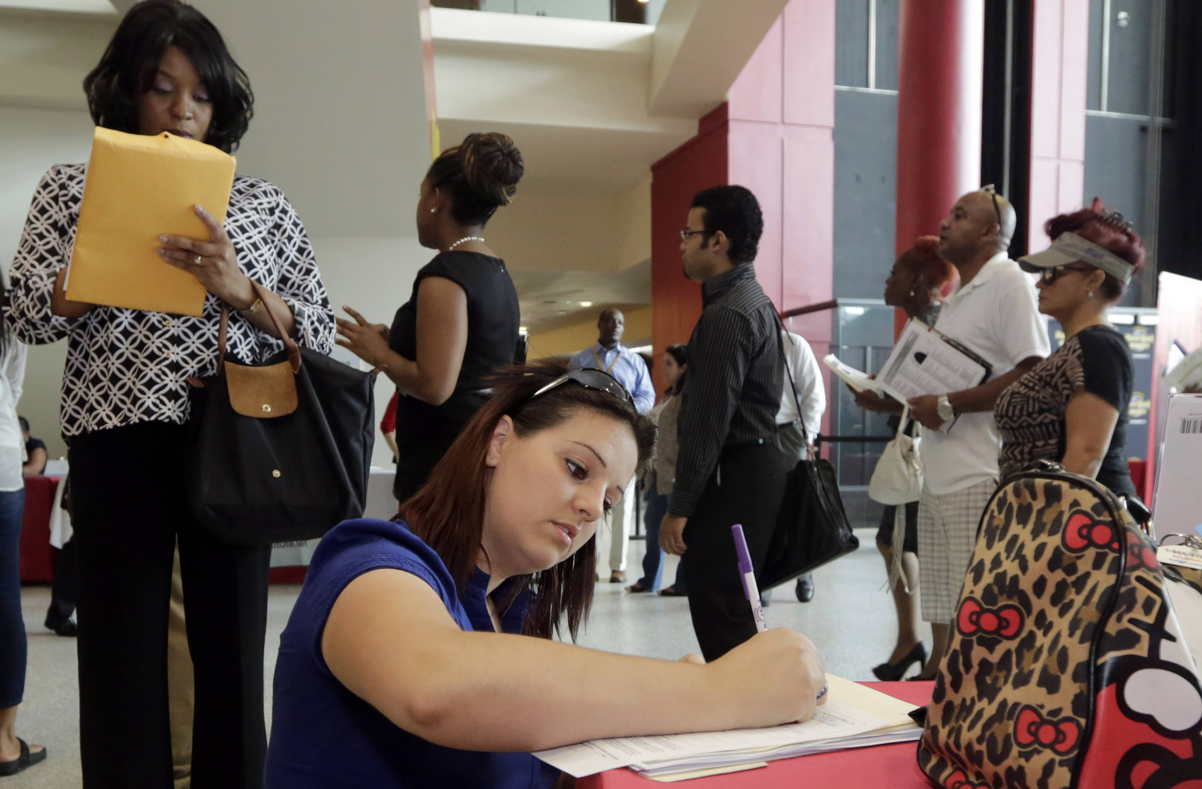 Jessica Pimentel, of Hollywood, Fla., fills out a job application during a job fair in Sunrise. Fla. The number of Americans seeking unemployment benefits slipped 1,000 last week to a seasonally adjusted 298,000, a low level that signals employers are cutting few jobs and hiring is likely to remain strong.