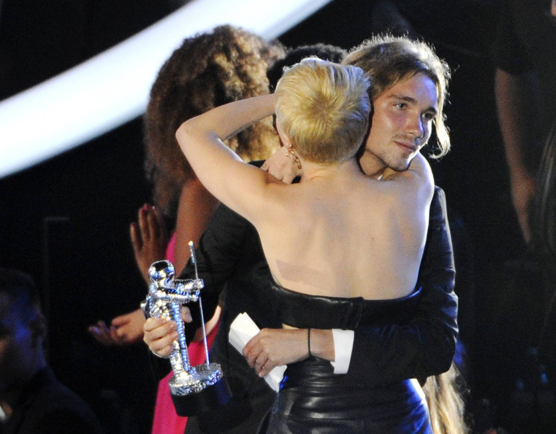 Miley Cyrus hugs Jesse Helt, right, at the MTV Video Music Awards Sunday. The young homeless man who accompanied Cyrus to the awards show gained worldwide attention when Cyrus let him accept her award for video of the year.