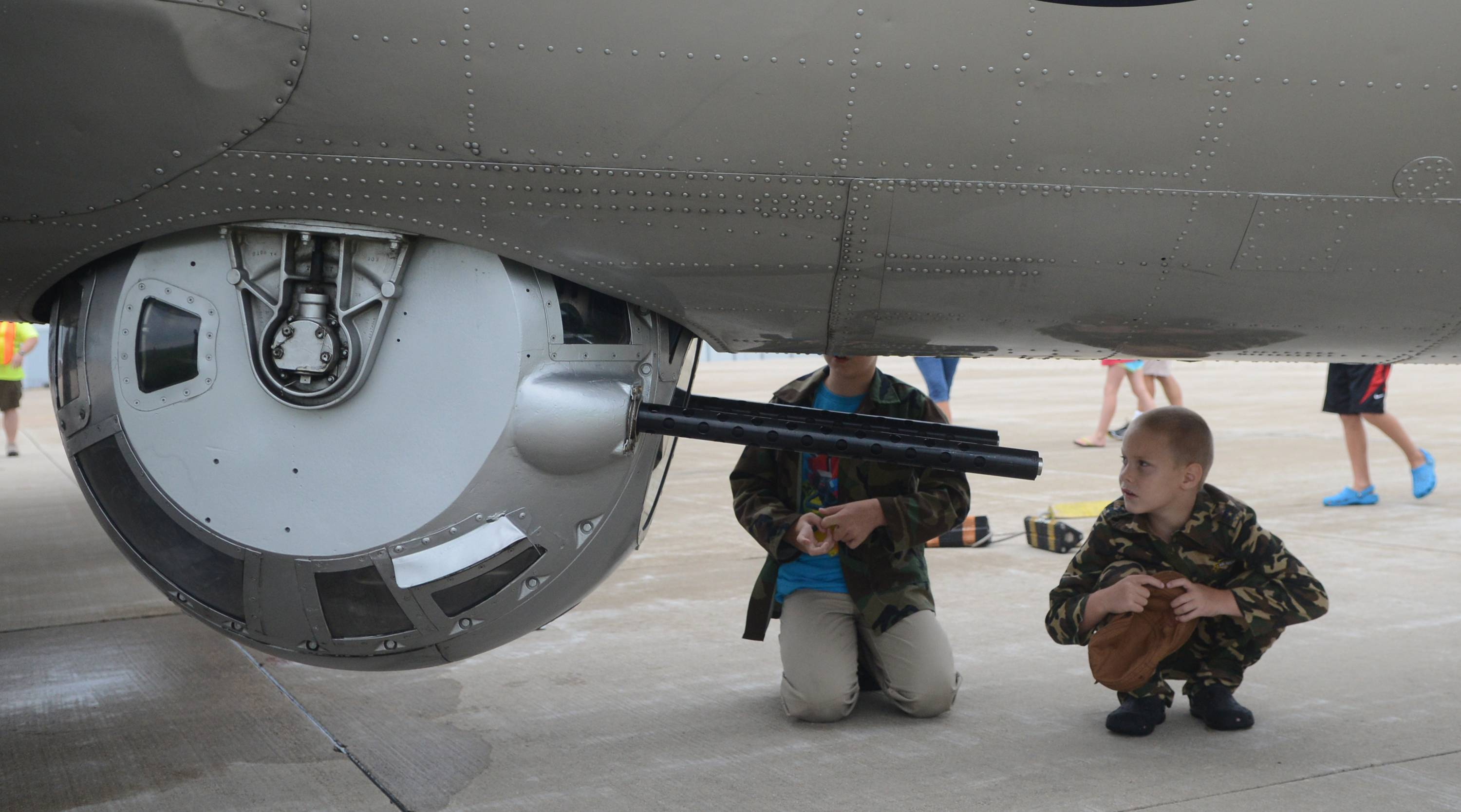 Jack Guyett, 6, right, and his brother, Tommy Guyett, 10, of St. Charles get a close-up look at the belly gun of a B-17 bomber Monday at the Aurora Airport. The EAA Warbird Squadron brought the World War II plane to the airport for the weekend and took it up for 30-minute flights.