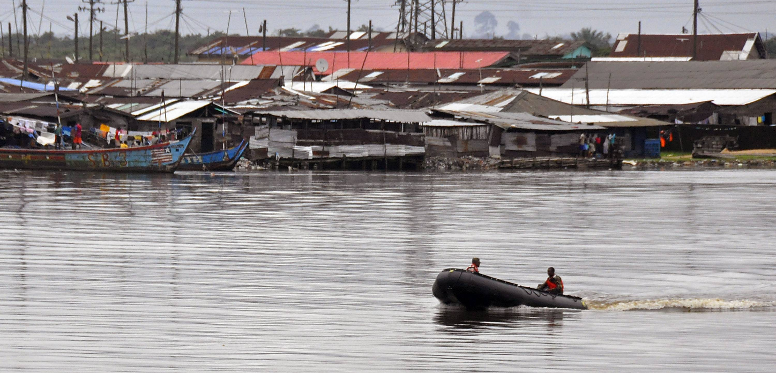 Liberian soldiers patrol the seaside of West Point Wednesday by boat, an area that has been hit hard by the Ebola virus, with local residents not allowed to leave the West Point area, as government forces clamp down on movement to prevent the spread of Ebola, in Monrovia, Liberia.
